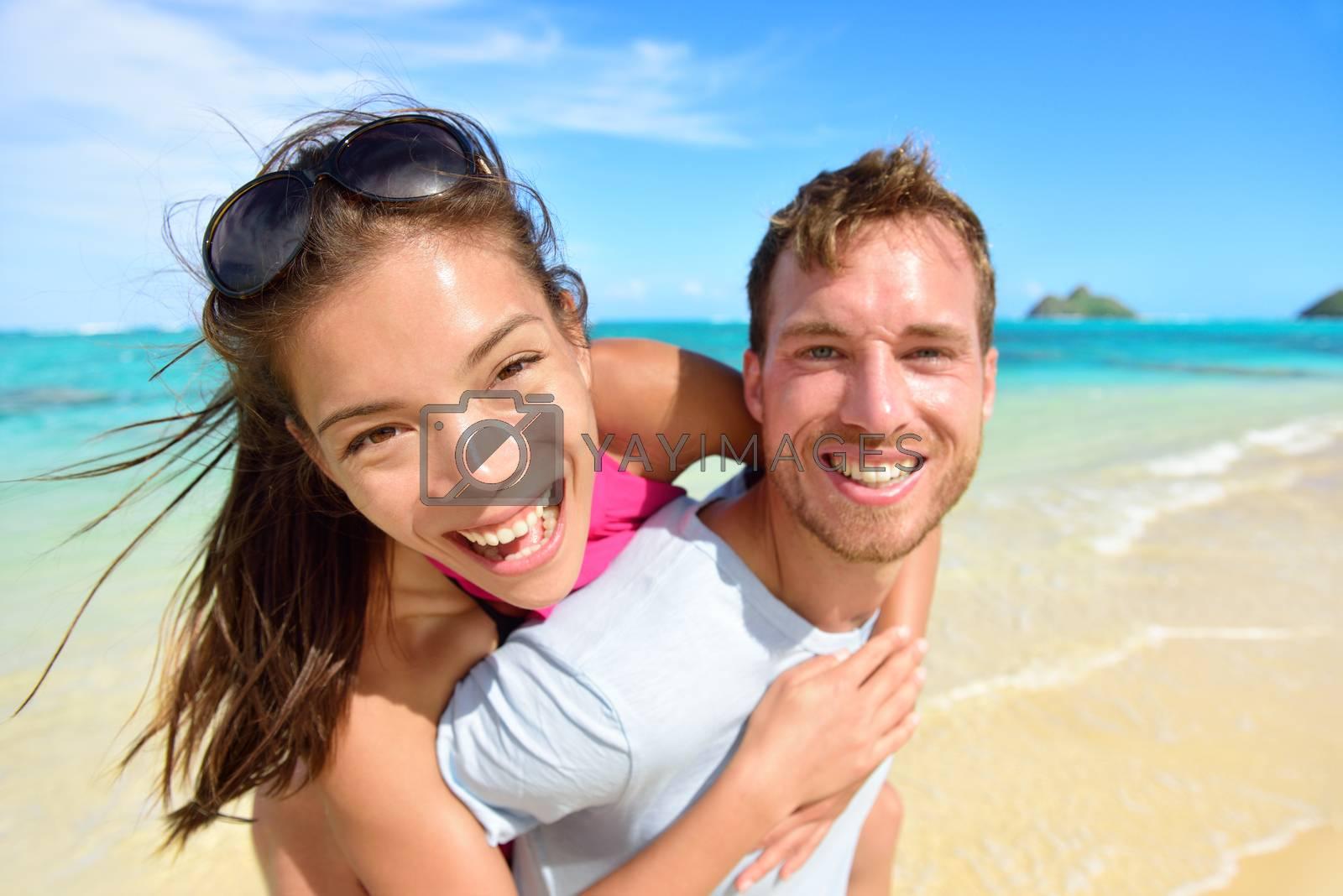 Happy beach couple in love on summer vacations on Lanikai beach, Oahu, Hawaii, USA with Mokulua Islands. Joyful Asian girl piggybacking on young Caucasian boyfriend and having fun on travel holiday.