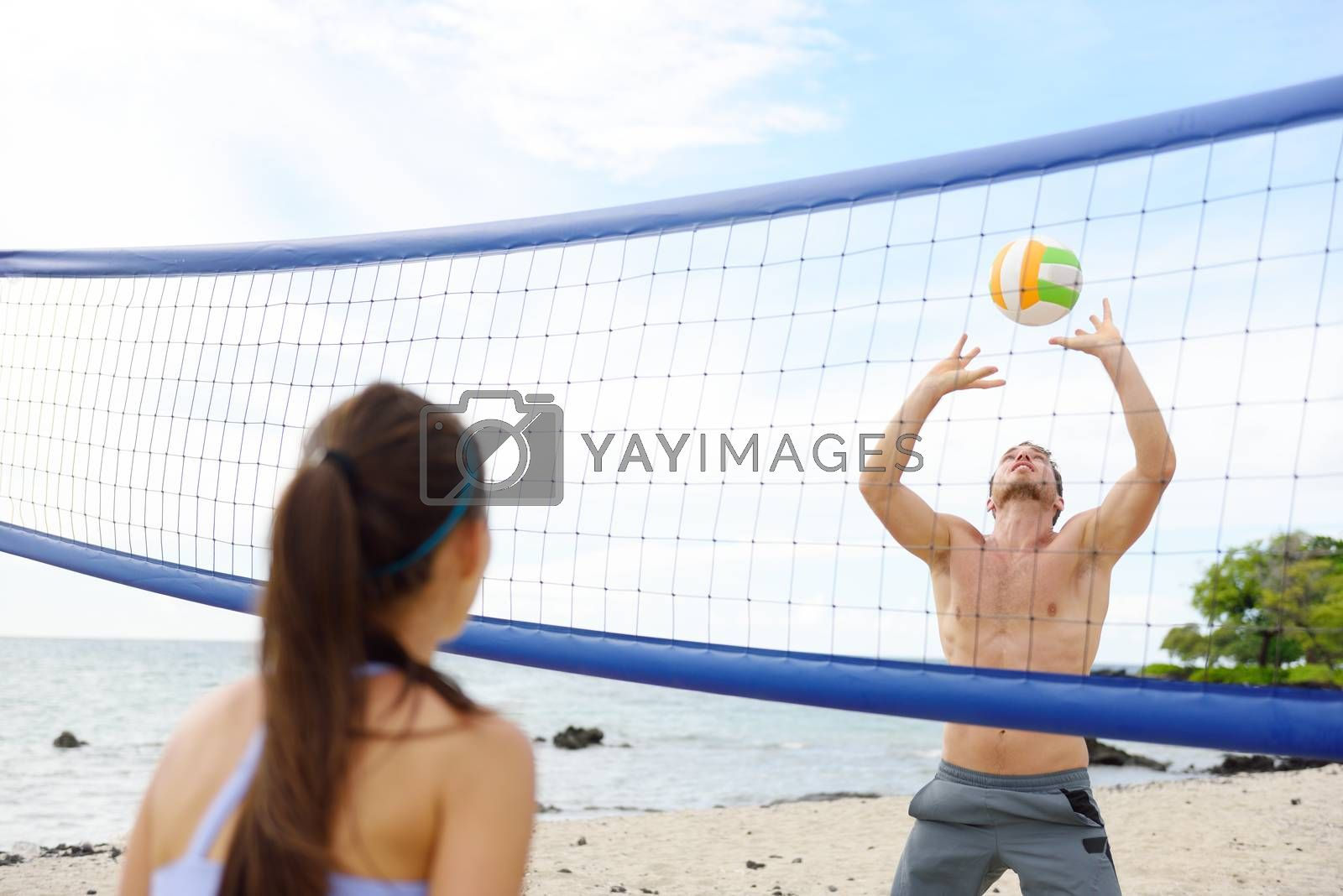 People playing beach volleyball having fun in sporty active lifestyle. Man hitting volley ball in game in summer. Woman and man fitness model living healthy lifestyle doing sport on beach.