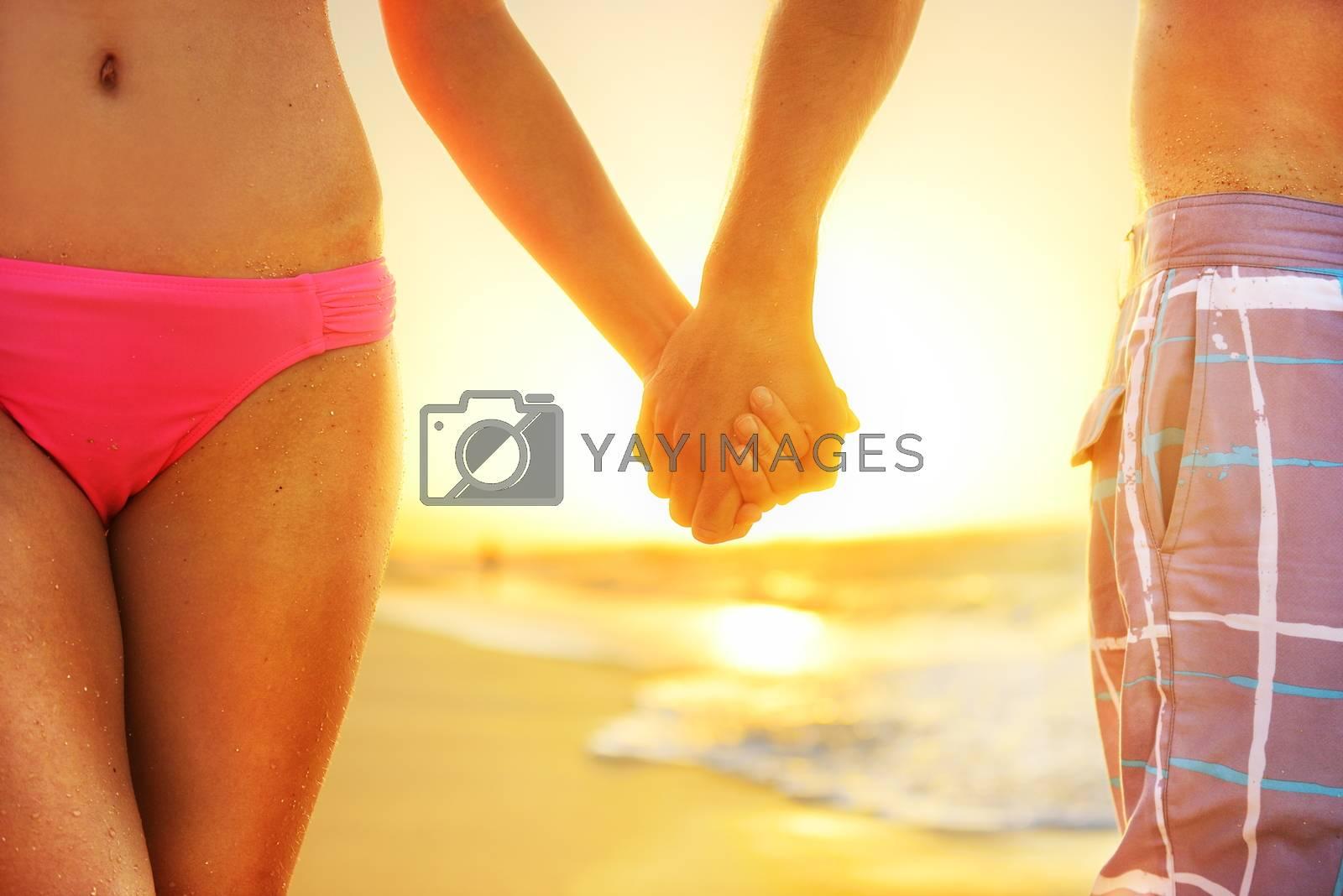 Beach sunset couple in love holding hands romantic on honeymoon. Bikini girl and casual beachwear man newlyweds people standing on travel summer vacations on tropical beach.