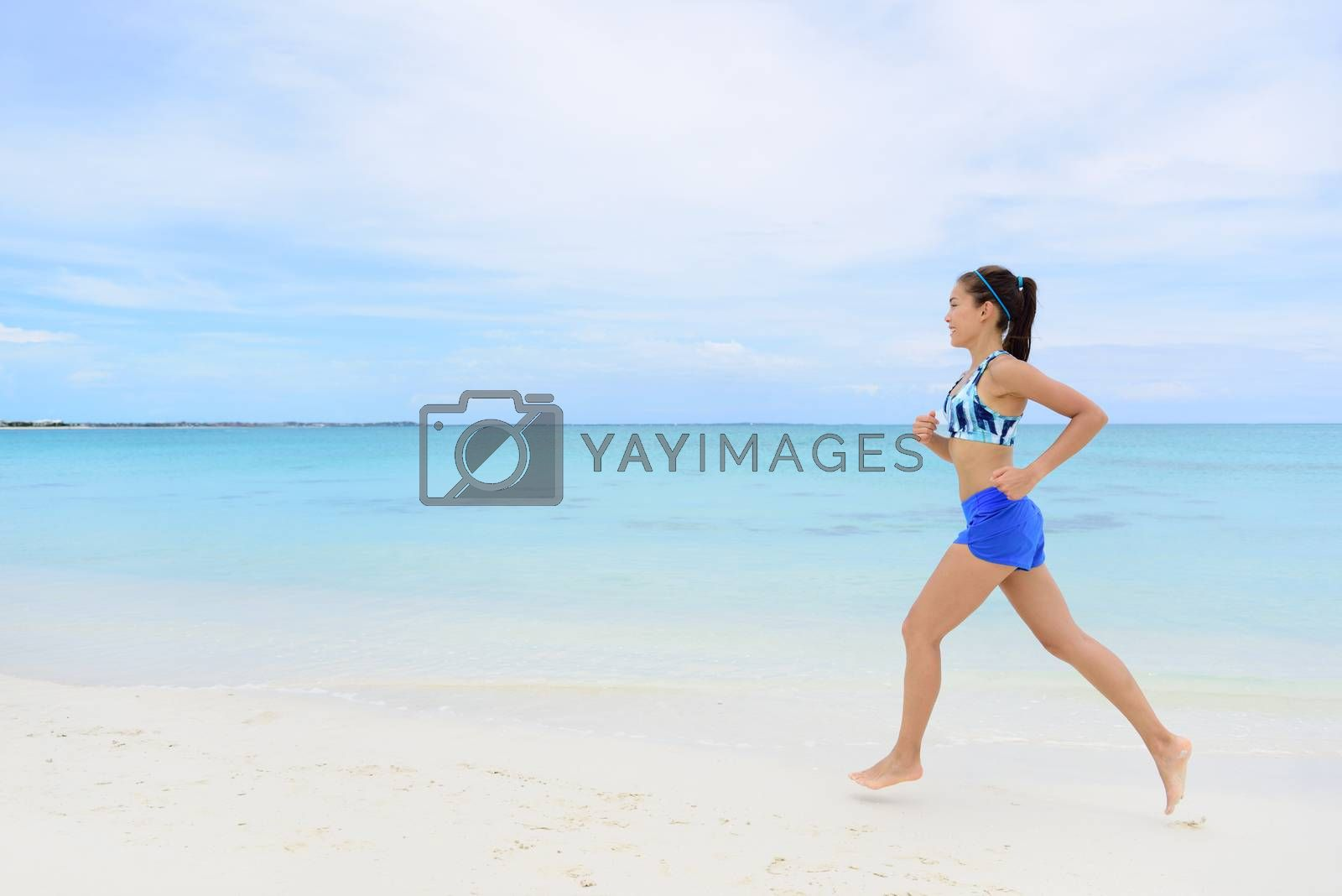 Healthy and active lifestyle running woman jogging on beach. Full length young female adult doing morning cardio workout barefoot in white sand and turquoise ocean background.