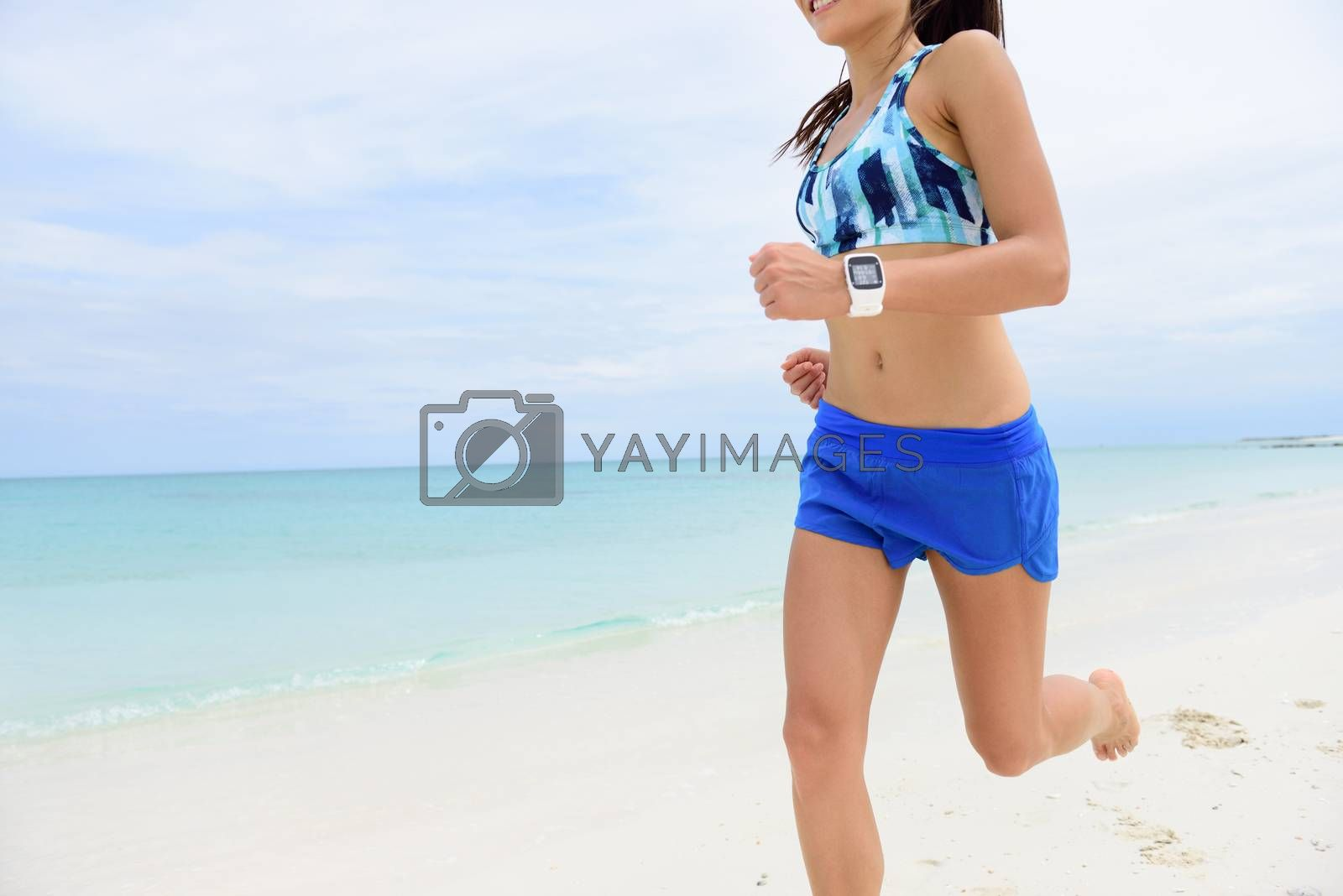 Runner running wearing smartwatch. Closeup of fitness woman wearing blue shorts and sports bra training cardio on beach using app on smart watch to monitor heart rate and speed.