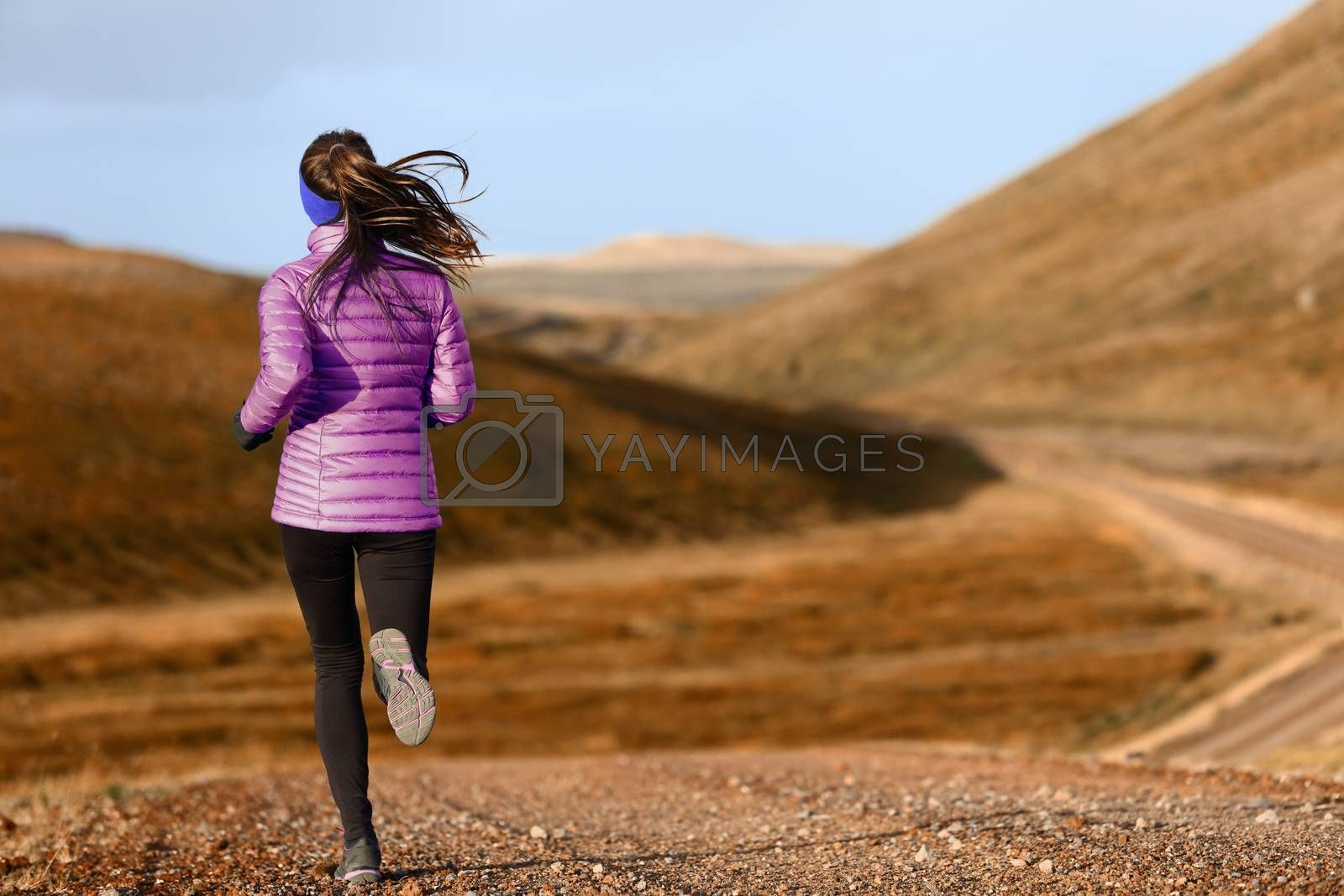 Woman trail runner running in mountain landscape. Female runner in warm clothes for autumn jogging cross country outdoors in foliage nature background.