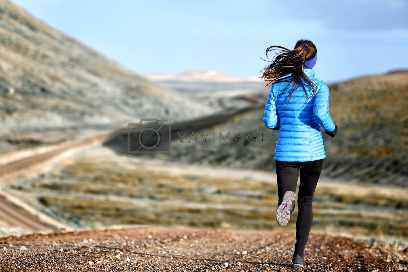 Woman winter and autumn running in down jacket by Maridav