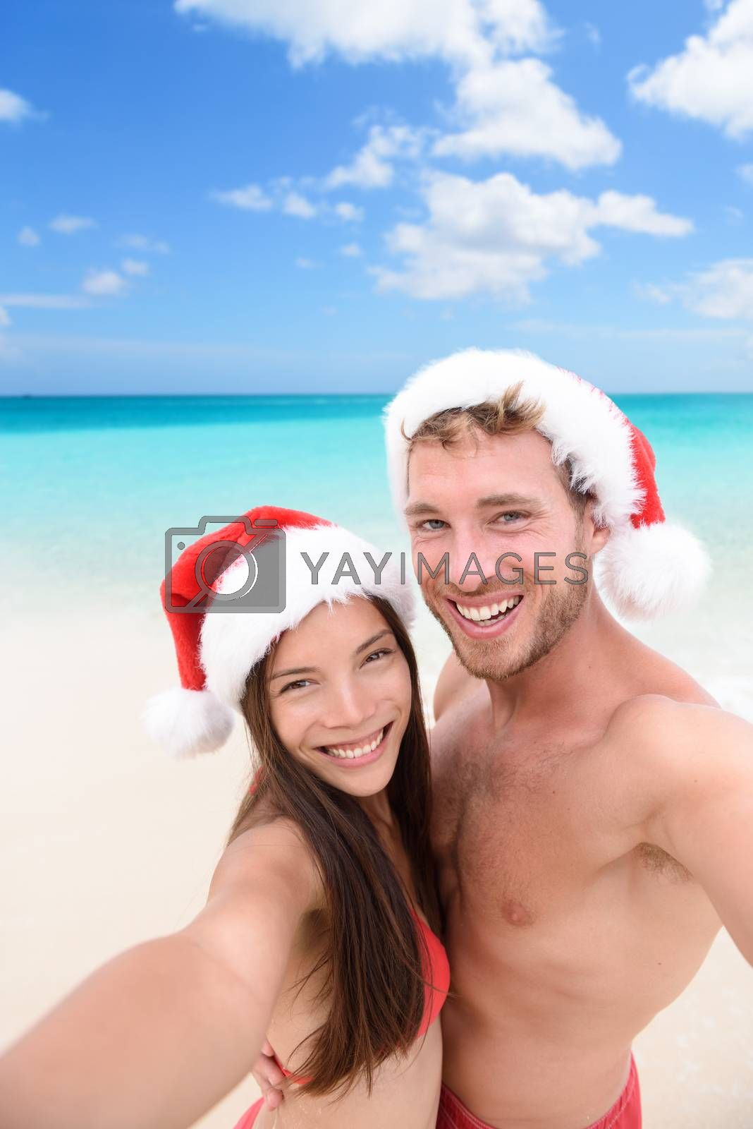 Happy couple on Christmas travel holidays taking selfie picture with smartphone wearing santa hat during their winter vacation. Young adult friends in swimsuit and bikini in front of the ocean.