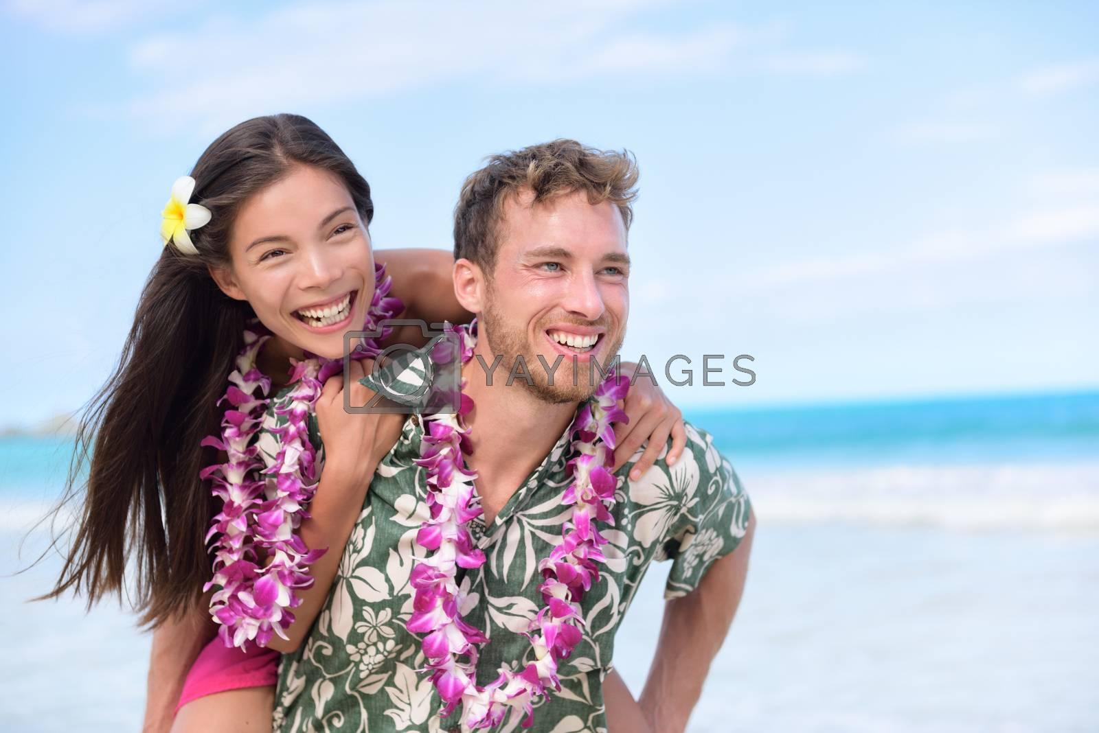 Happy beach couple having fun piggybacking and laughing on Hawaii travel holiday. Beautiful Asian mixed race woman abd Caucasian boyfriend wearing traditional Hawaiian lei on Oahu, Hawaii, USA.