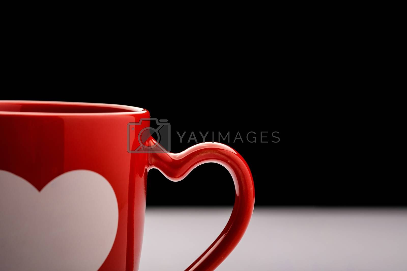 A burgundy coffee mug with heart shaped handle on white table with dark background.