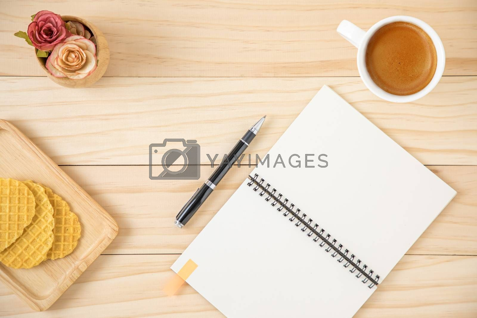 A blank notebook and a cup of coffee in white ceramic cup. Wooden background.
