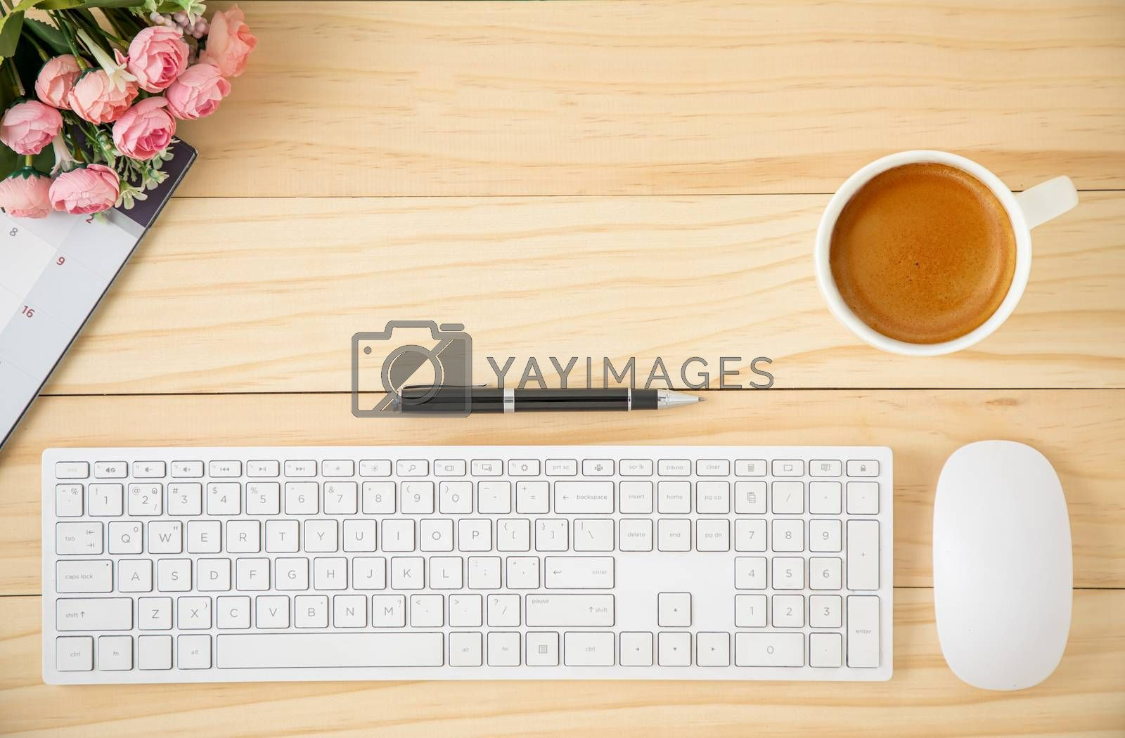 A minimal business workspace with white wireless computer mouse and keyboard with coffee in a white ceramic cup.