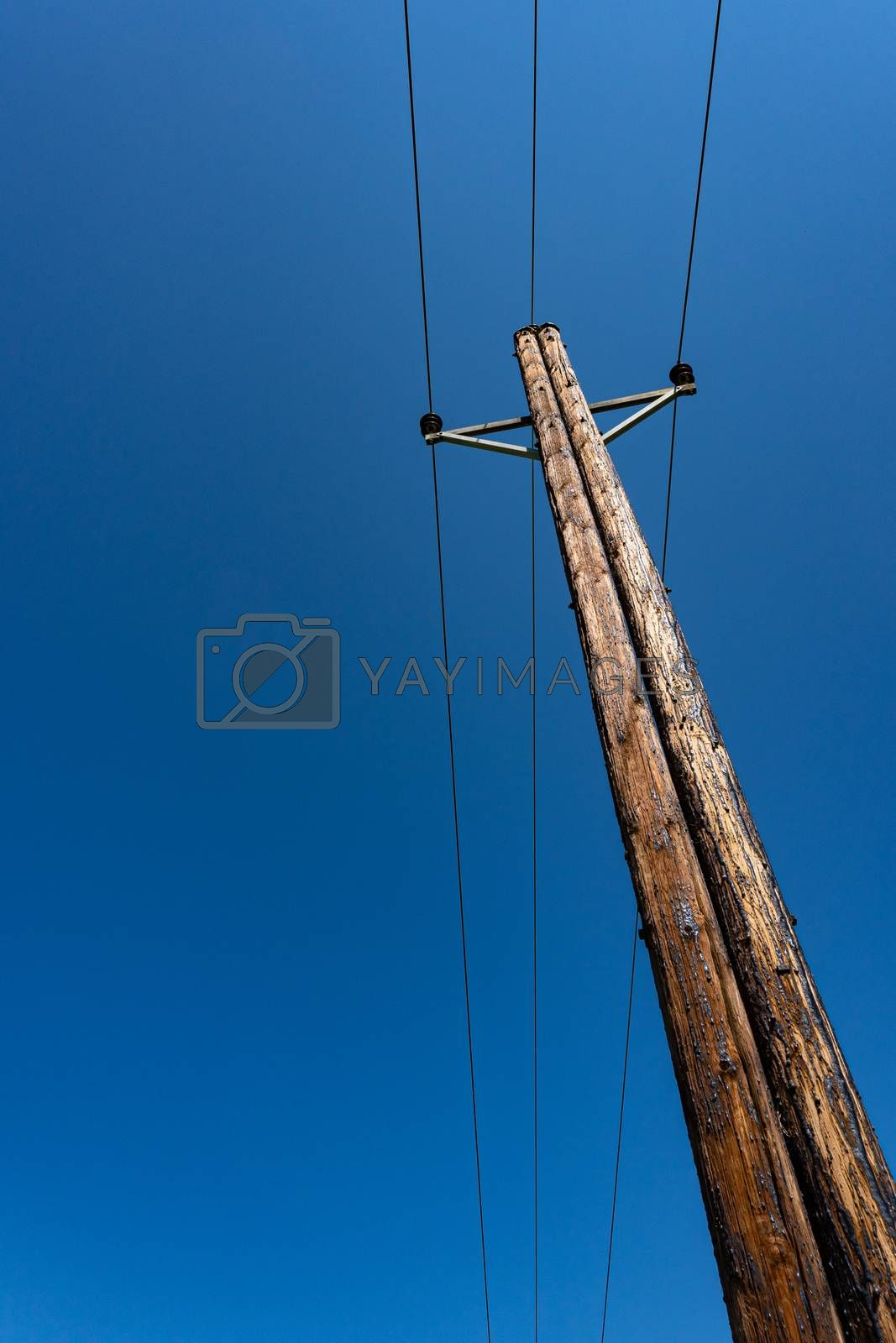 Telephone pole with wires for communication on blue sky. Vertical photo