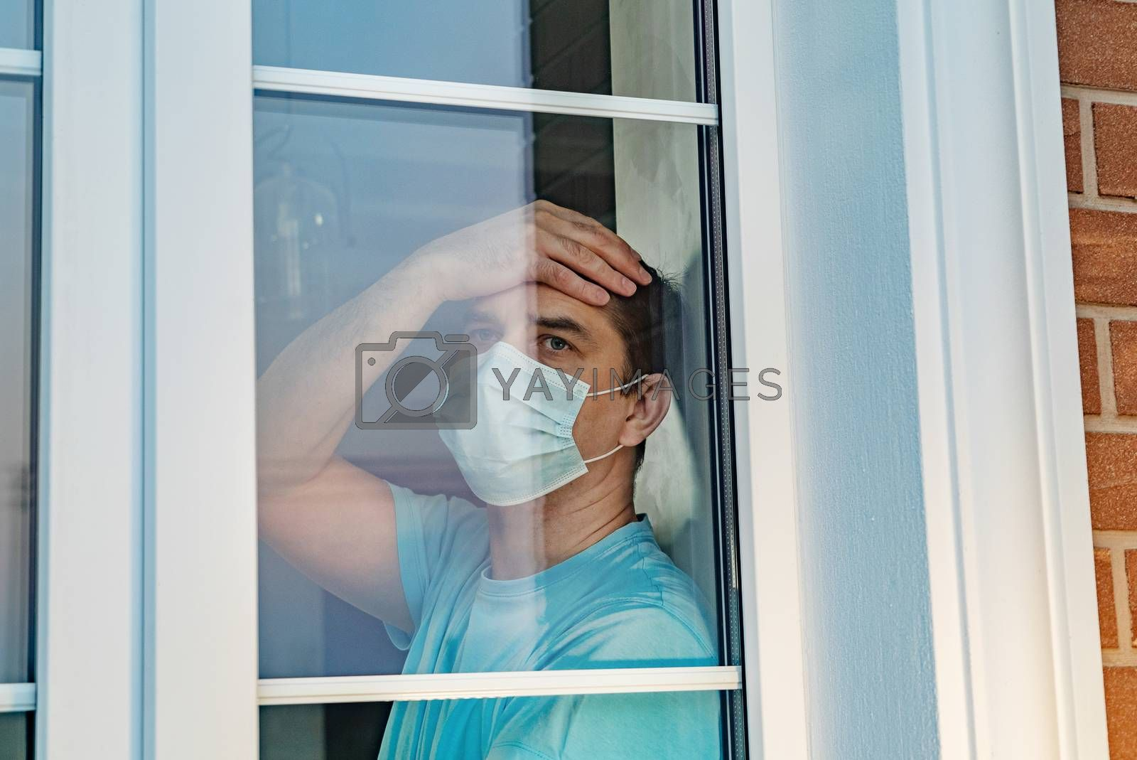 COVID-19. Sick man of coronavirus looking through the window and wearing mask protection and recovery from the illness in home. Quarantine isolation COVID19. Sick isolated at home to prevent infection