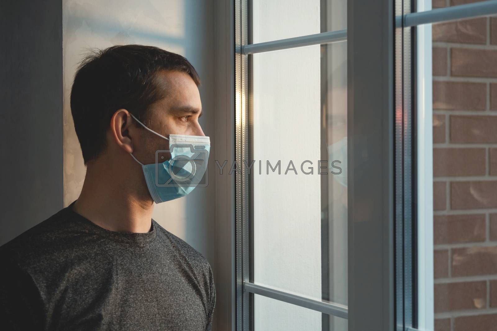 Quarantine self-isolation. Sad young man in a medical mask who looks out the window through the window. Infected man in medical mask on self-isolation looks at the street through the window of a house