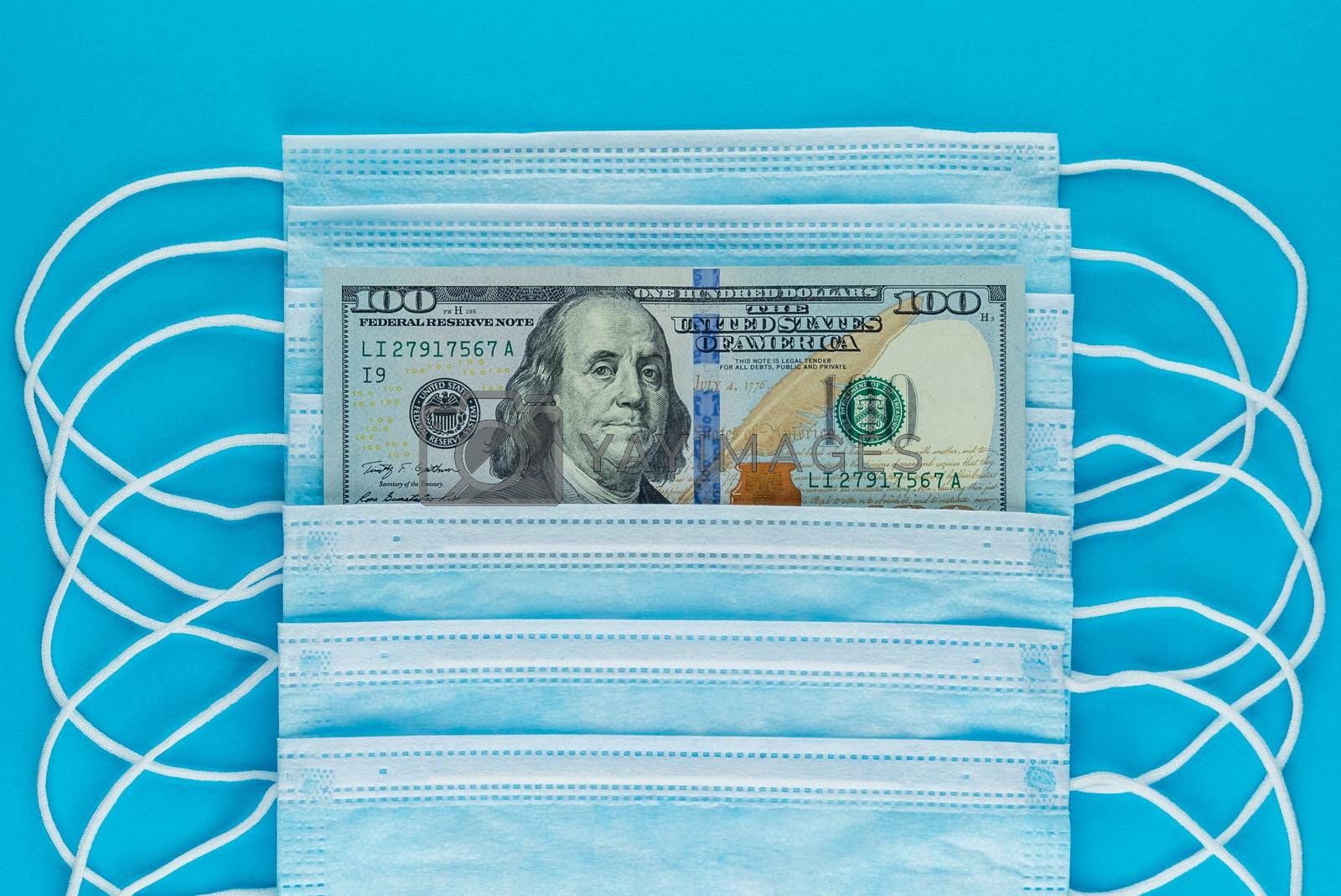 Blue medical masks, and american money, flat lay. 100 dollar bill in a stack of medical masks, top view. The rise in price of medical masks. Financial assistance for medicine. US Medical Mask Exports
