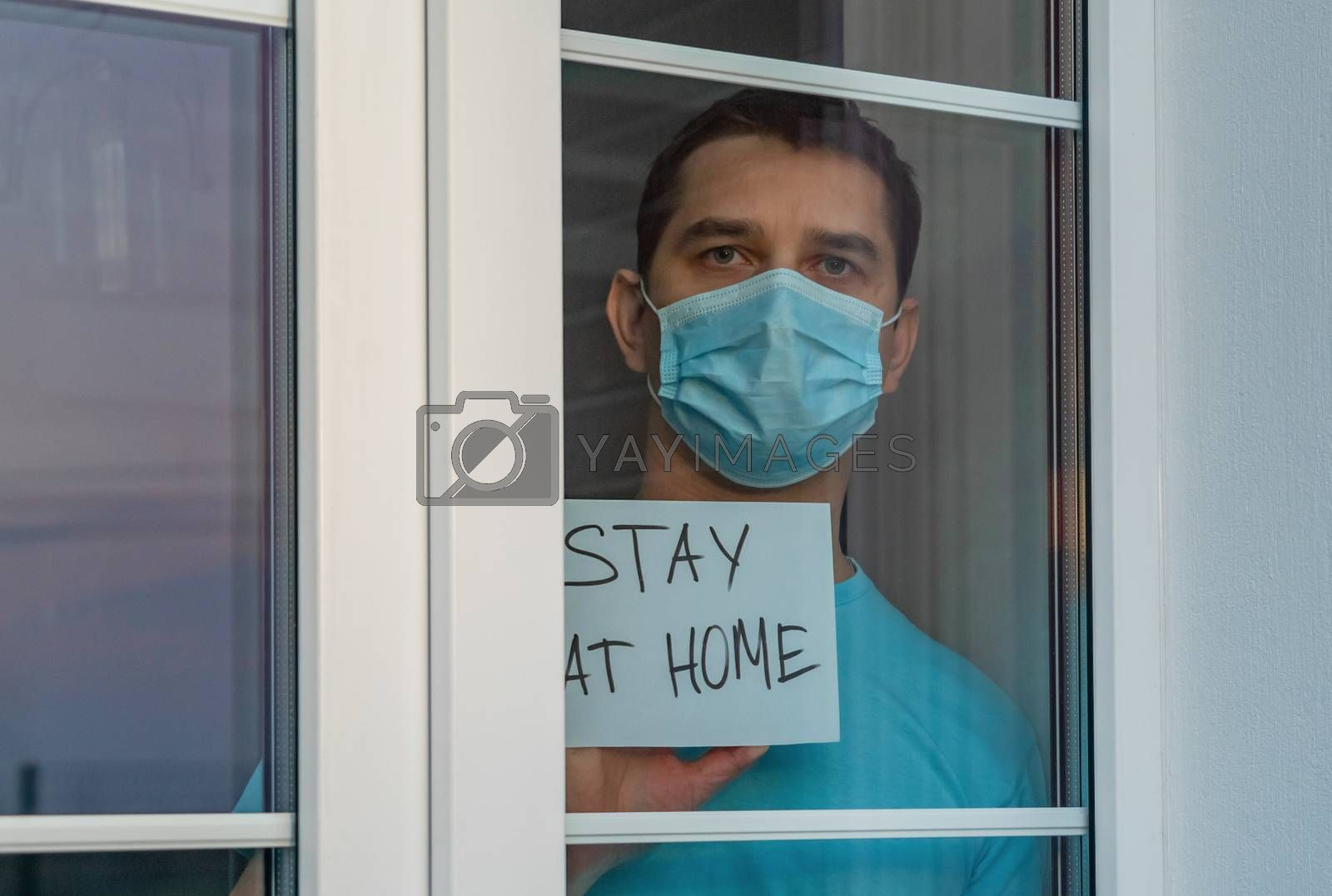 Medical mask, protection against coronavirus and other viruses. Young attractive man in a blue clothes with medical mask showing a nameplate with the lettering Stay at home. Self isolation COVID-19