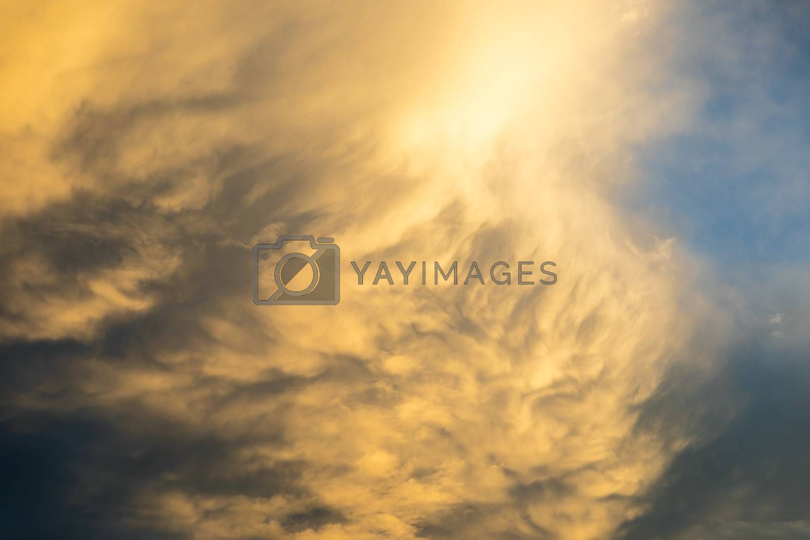 Rolling golden clouds on overcast sky during sunset. by jack-sooksan