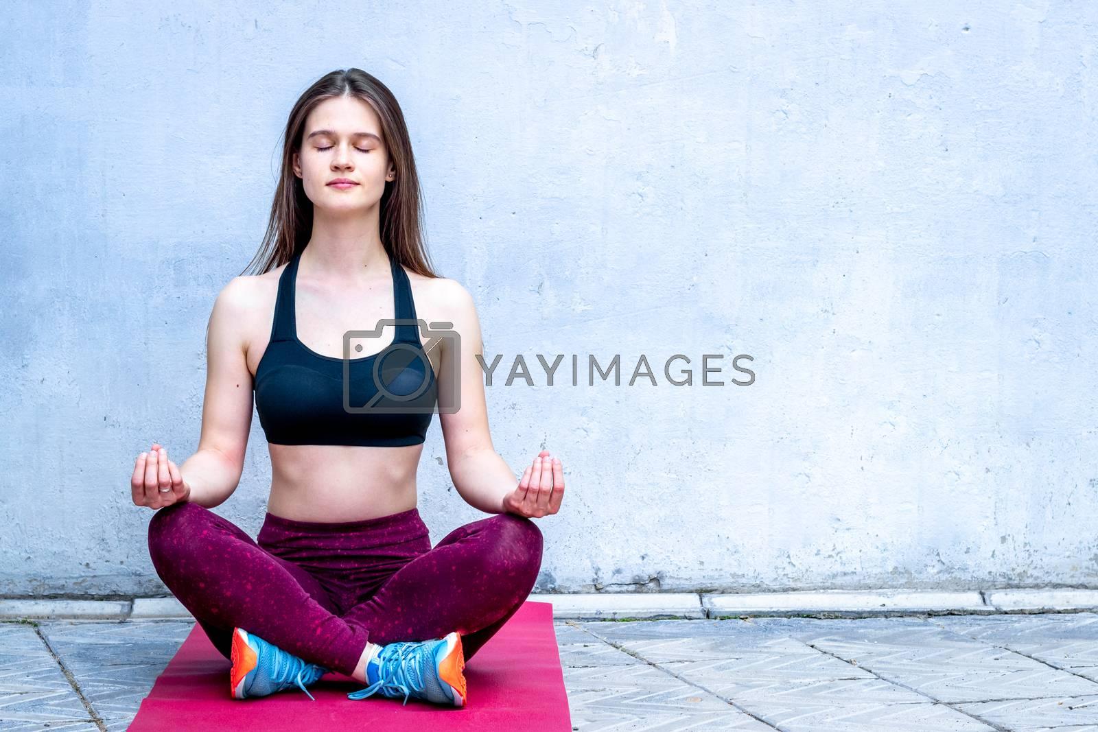 Meditation. Girl in sport wear relax in yoga asana - blue wall, copy space by 9dreamstudio