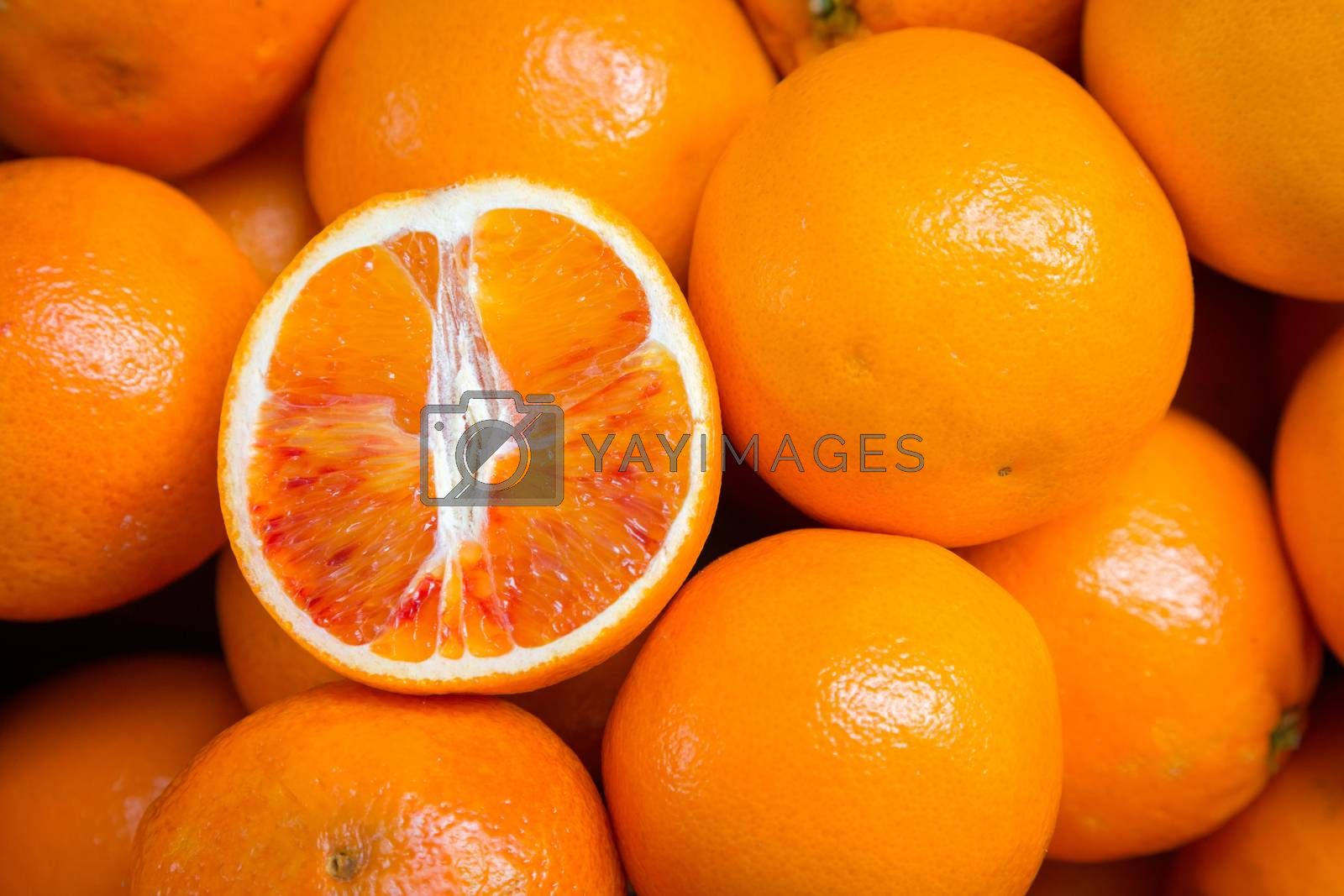 Citrus fruits background. Fresh tangerines oranges on market. Group of freshly picked oranges with their leaves forming a background. Top view of slices, whole of orange fruits and leaves close up.