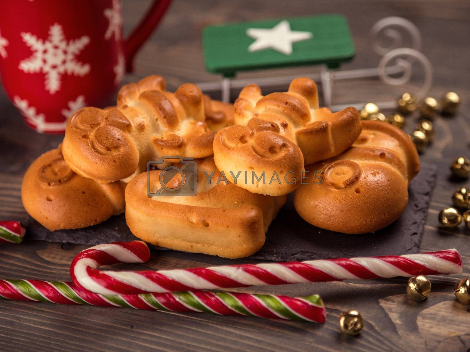 Christmas cookies homemade on brown wooden background. Table top shot of a nicely decorated Christmas cookies on rustic wooden table. Christmas background with ruddy gingerbread and homemade cookies.