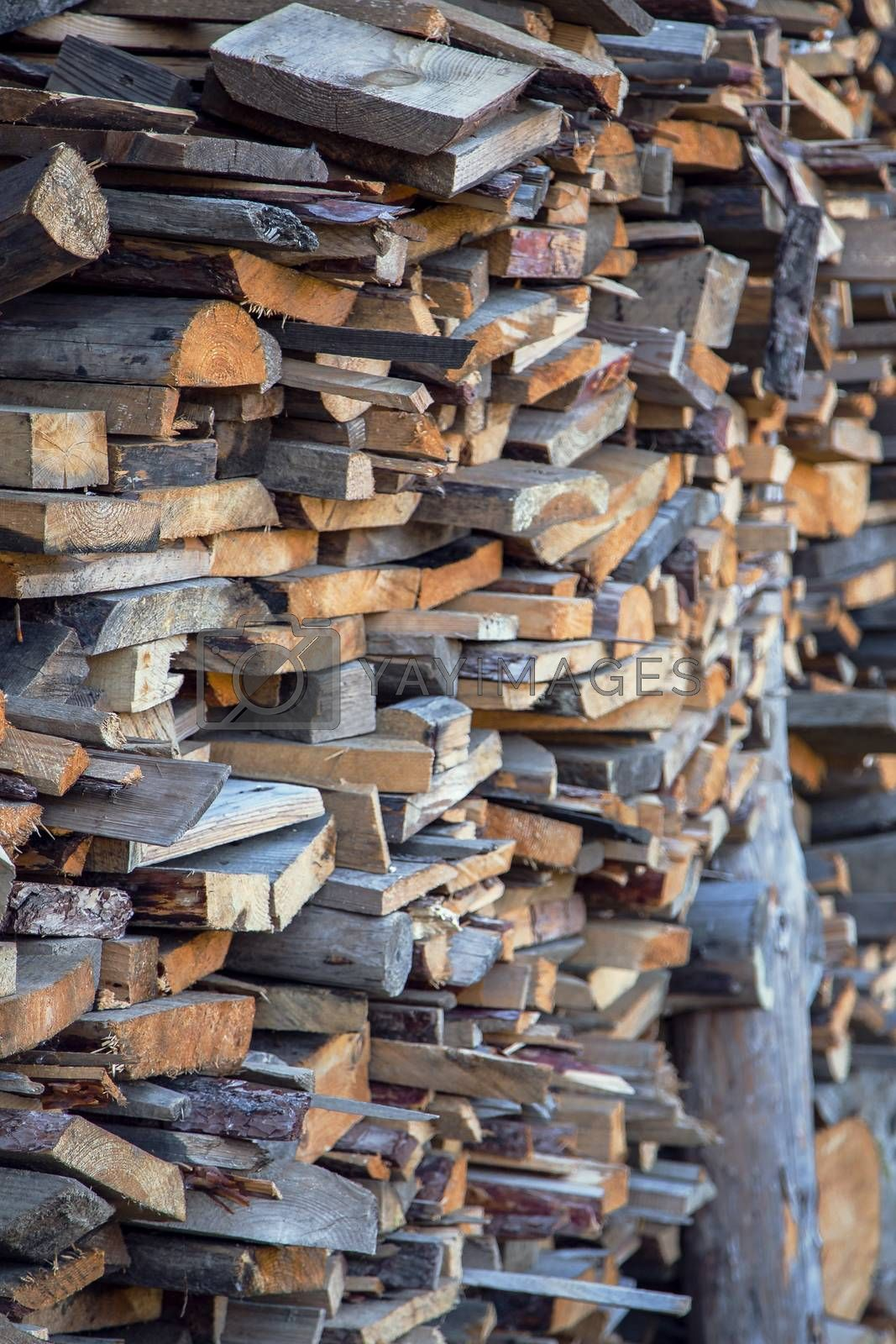 Pile of chopped fire wood prepared for winter. Stack of chopped firewood prepared winter. Stocking up of firewood. Firewood background - chopped firewood on a stack. Selective focus on a foreground.