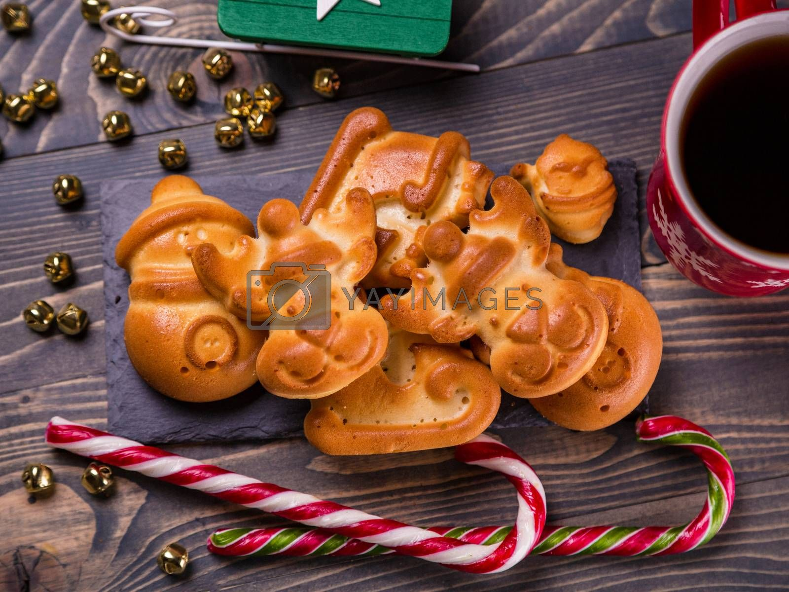 Background with tasty cookies, cup of coffee and Christmas decor on wooden table. Greeting card with gingerbread cookies. Close up, top view. Merry Christmas and Happy New Year. Homemade cookies.