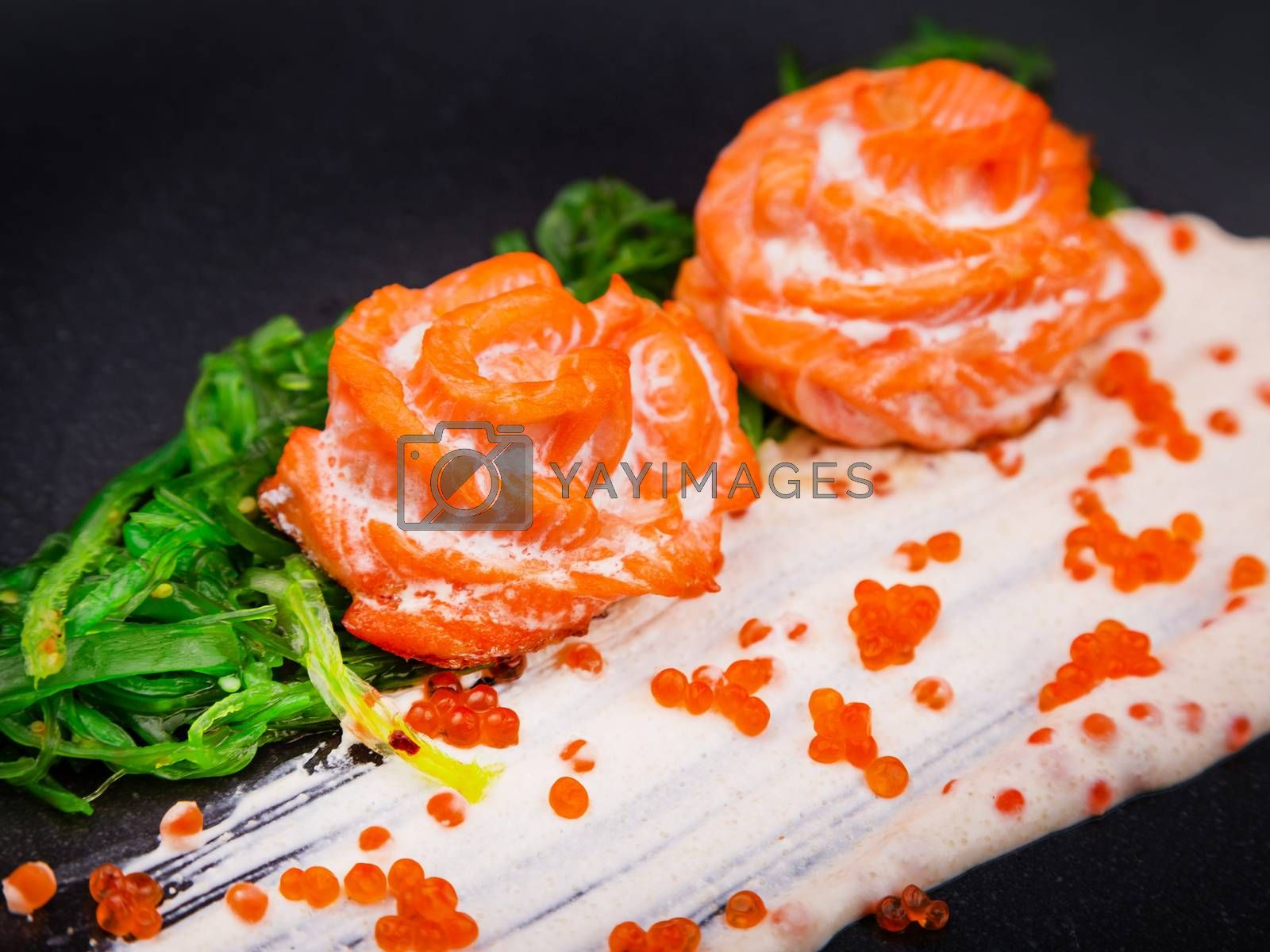 Cooked baked salmon in cream sauce garnished with hiyashi algae and red caviar, served on a black plate. Designer decorated dishes with salmon. Salmon fillet with green salad and red caviar.