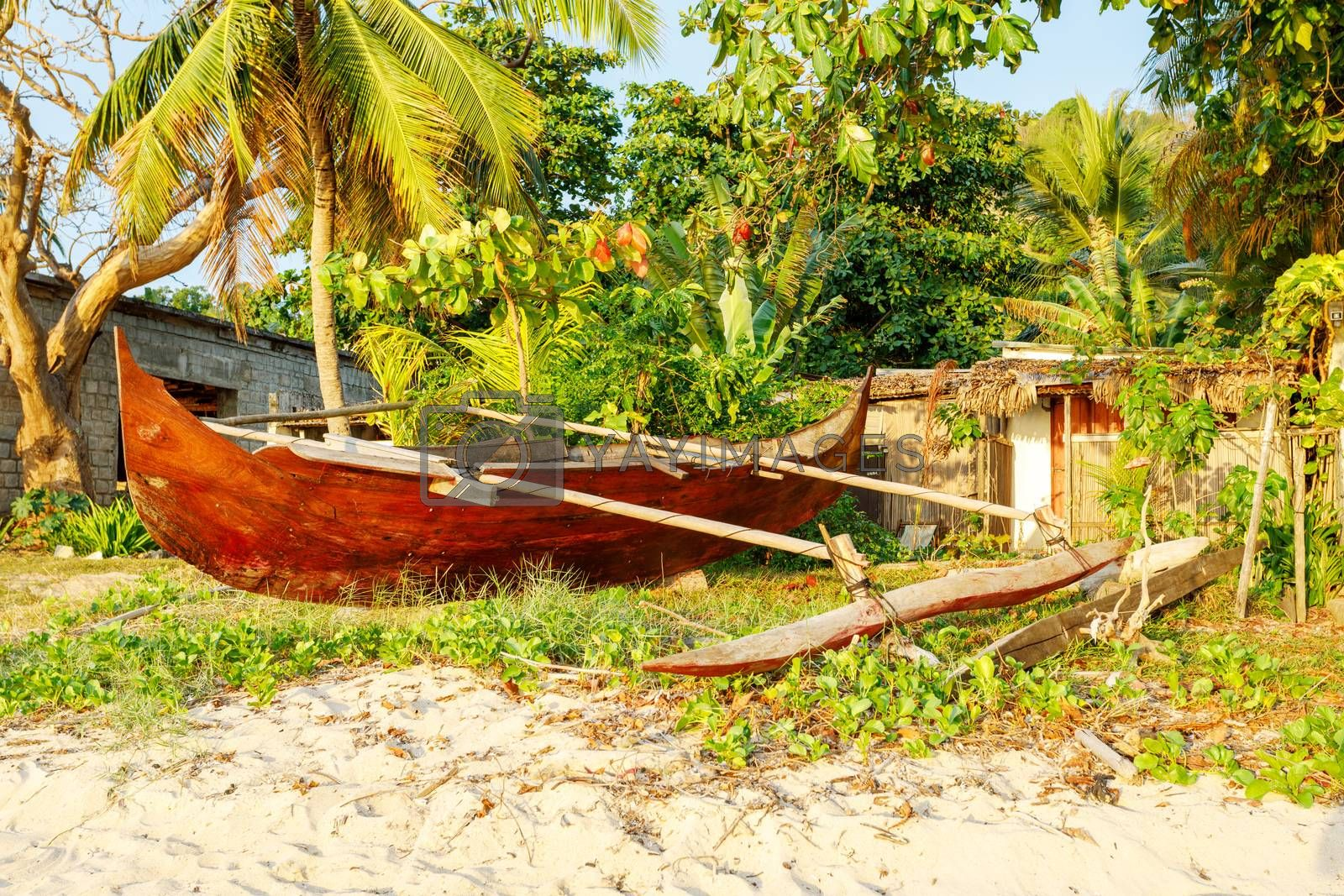 Traditional aboriginal Malagasy wooden hand made fisherman dugout catamaran boat the beach in Nosy Be, Indian ocean, Madagascar
