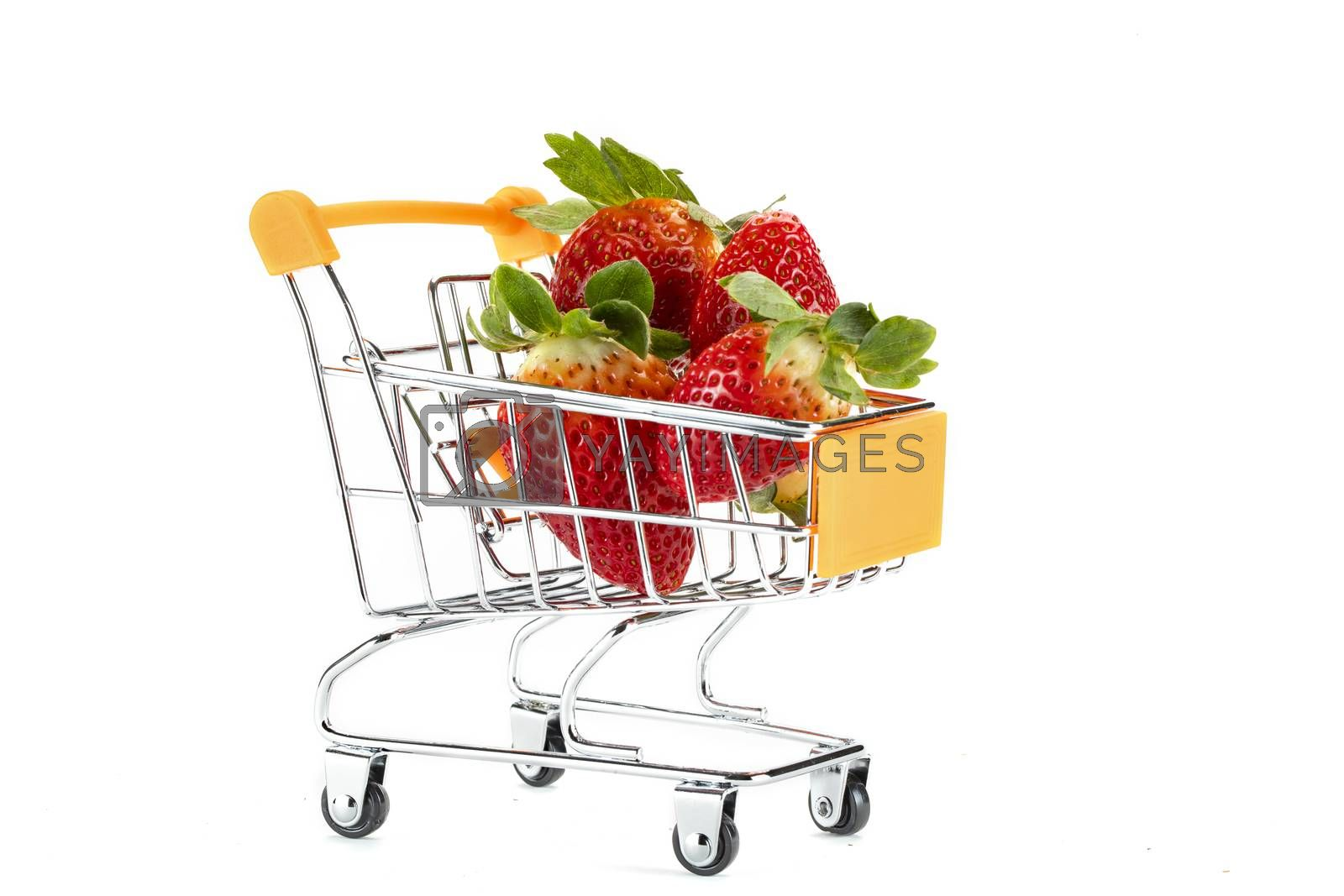 A bunch of red fresh strawberries on a toy shopping cart. Isolated on white background.