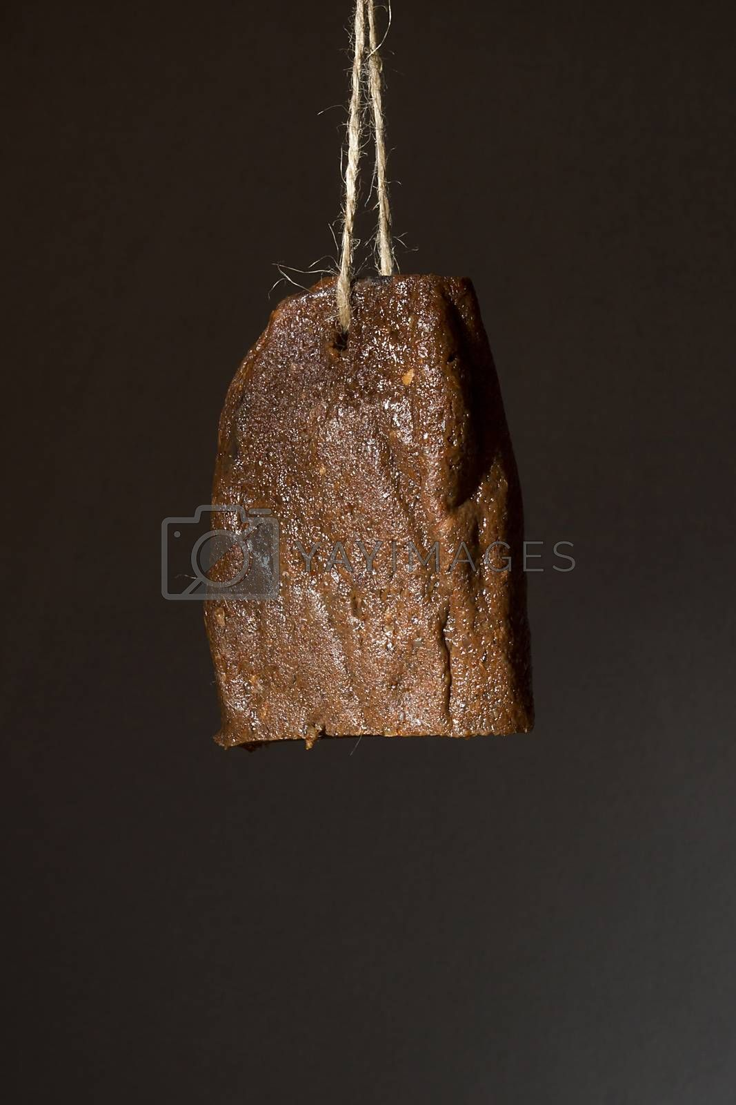 Jerky beef hanging on a rope against a black wall