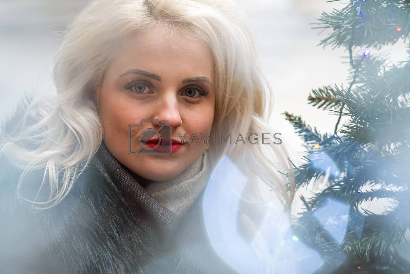 Portrait of a young smiling blonde woman photographed through the Christmas lights, soft focus - image
