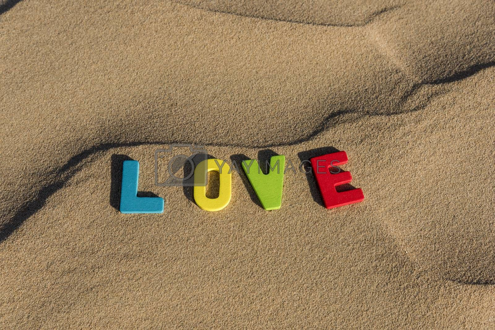 LOVE word written with colorful letters on soft sand of the desert