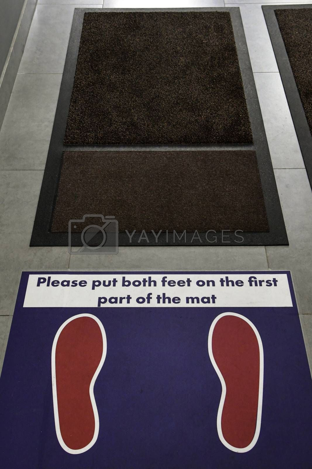Floor markings and instructions for shoe sanitizing mats in an office building during the covid 19 pandemic.