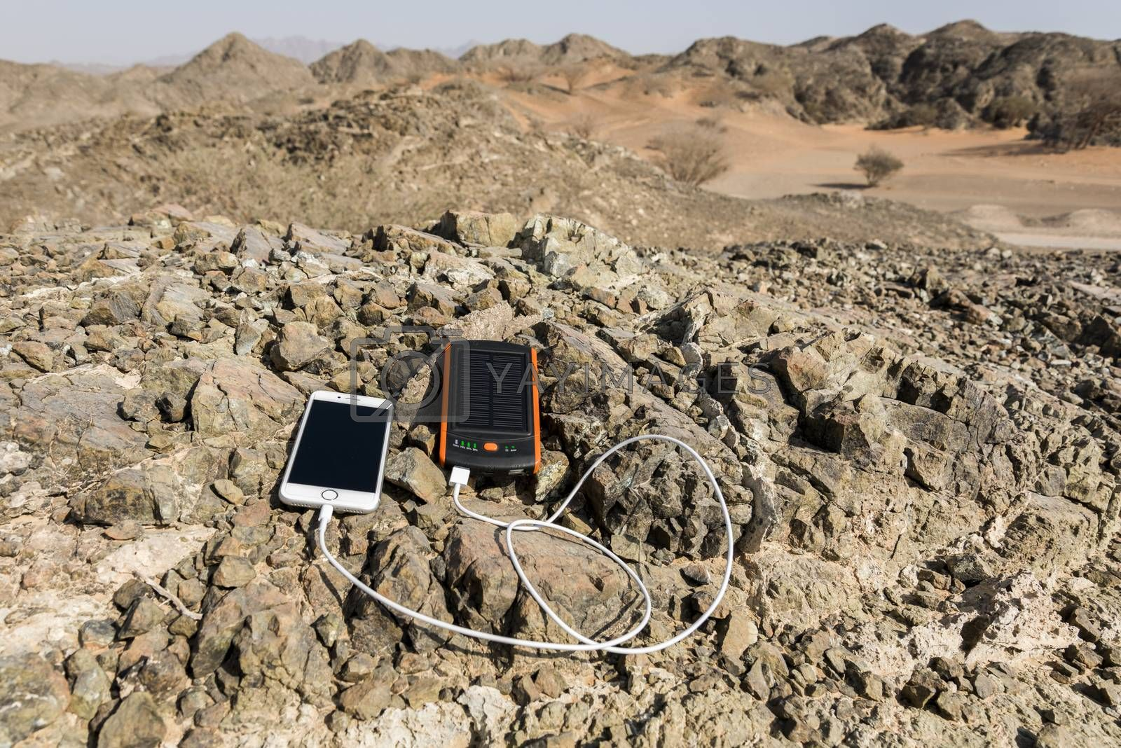 Smartphone charging with solar power bank with Dual USB port. These gadgets are lying on rocks, in the deserted mountain with some sand dunes in background.