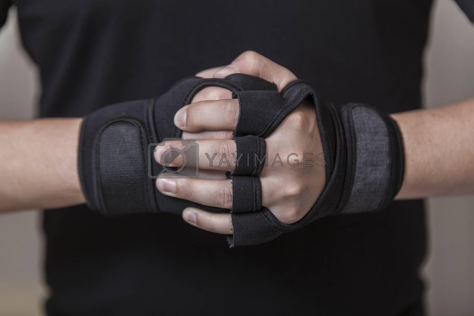 Man's hands put on sports gloves for a gym