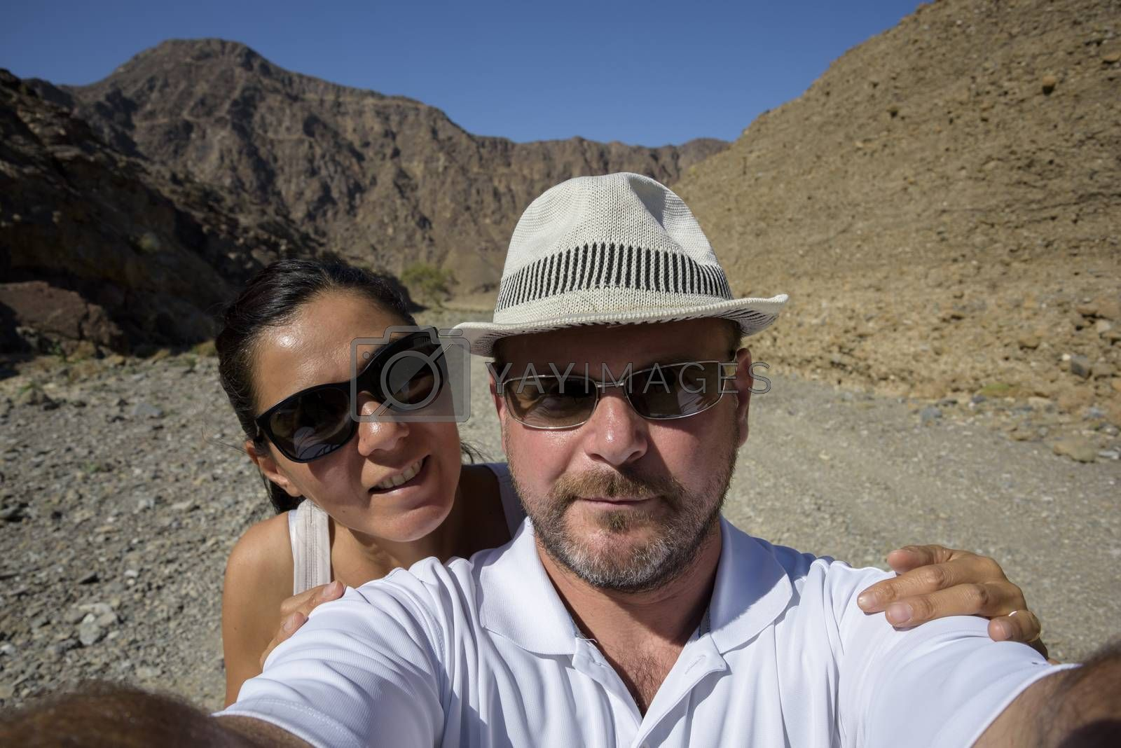 A couple in the 40s taking a selfie in a Wadi (dry riverbed) in the United Arab Emirates.