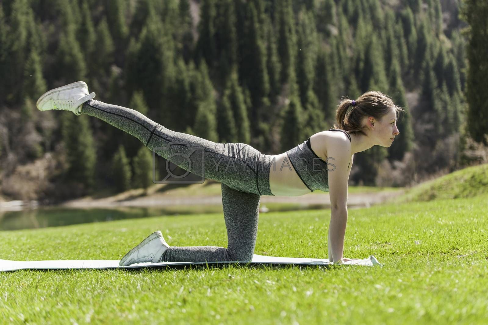 The girl on a green lawn practices yoga, costs in a pose