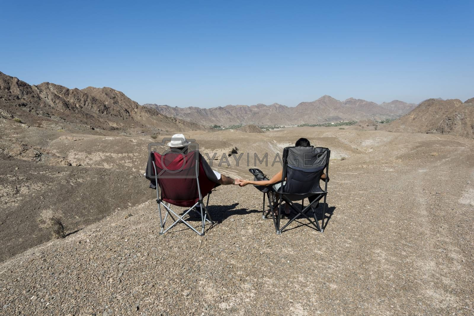 Couple in camping chairs over-looking a Wadi, mountains, in The United Arab Emirates