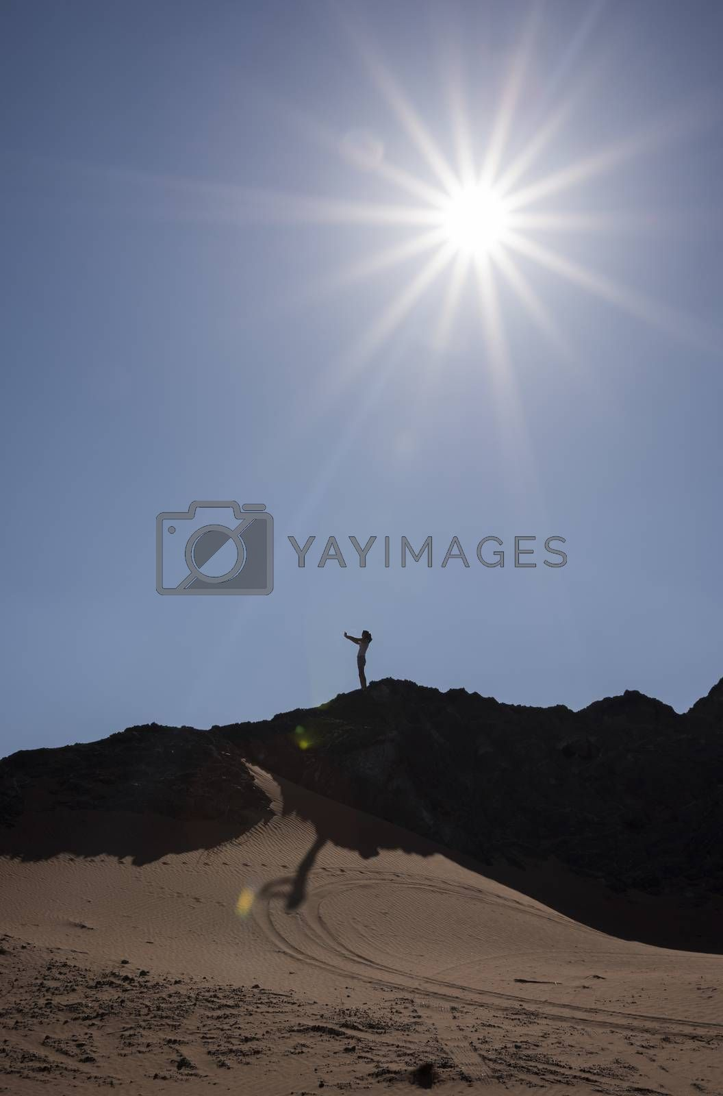 Woman taking a selfie in a mountain in the desert with contre-jour.