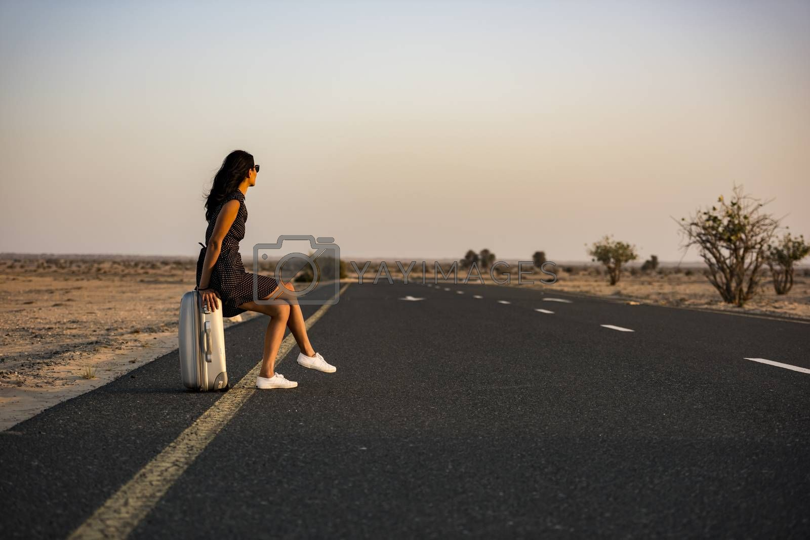 Woman waiting with her luggage on rural road in the desert for a lift or a vehicle to come