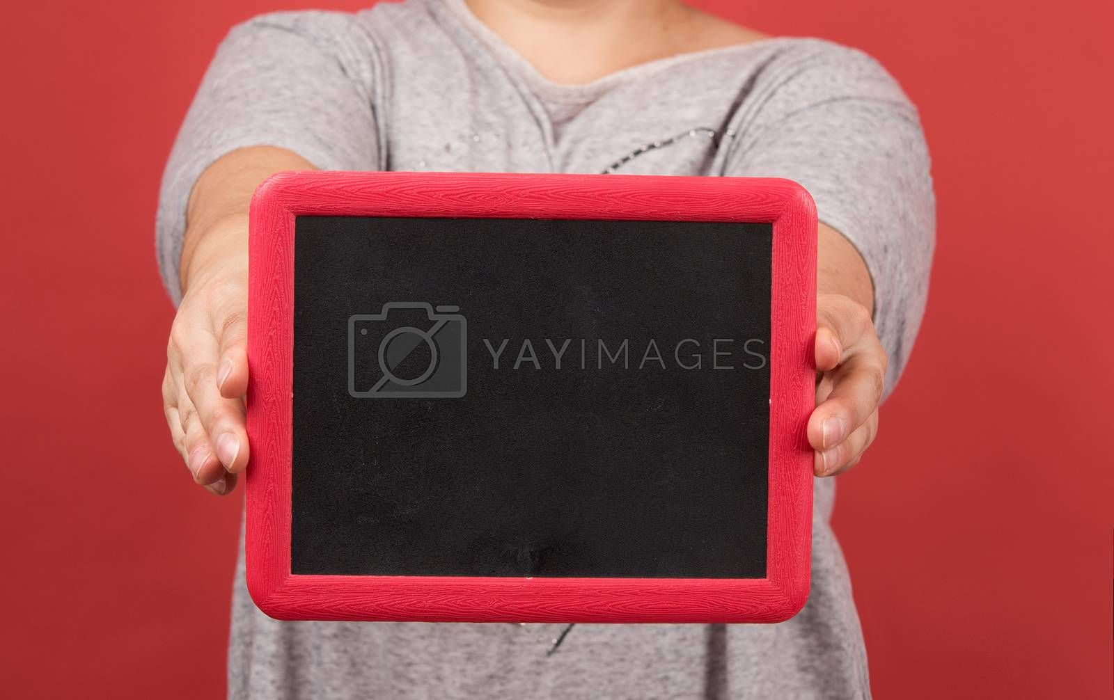 woman holds empty  frame on red background, place for an inscription