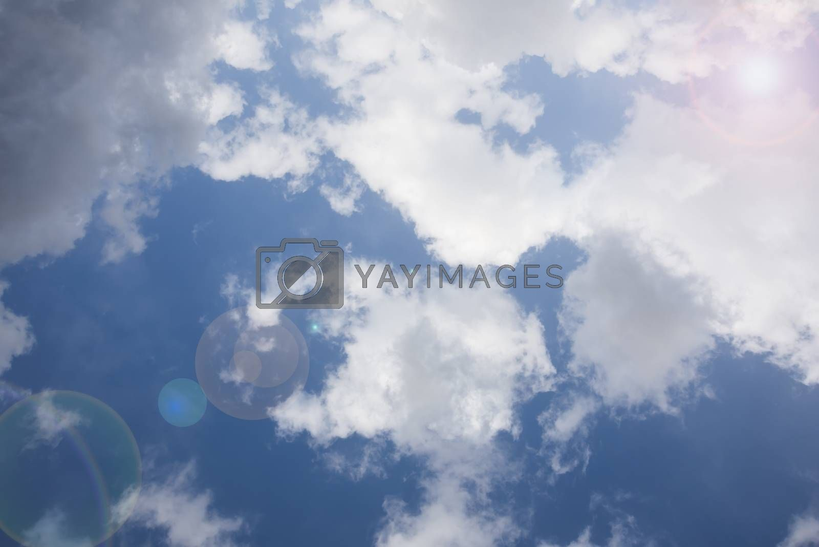 Blue sky with white clouds, sun and lens flare effect