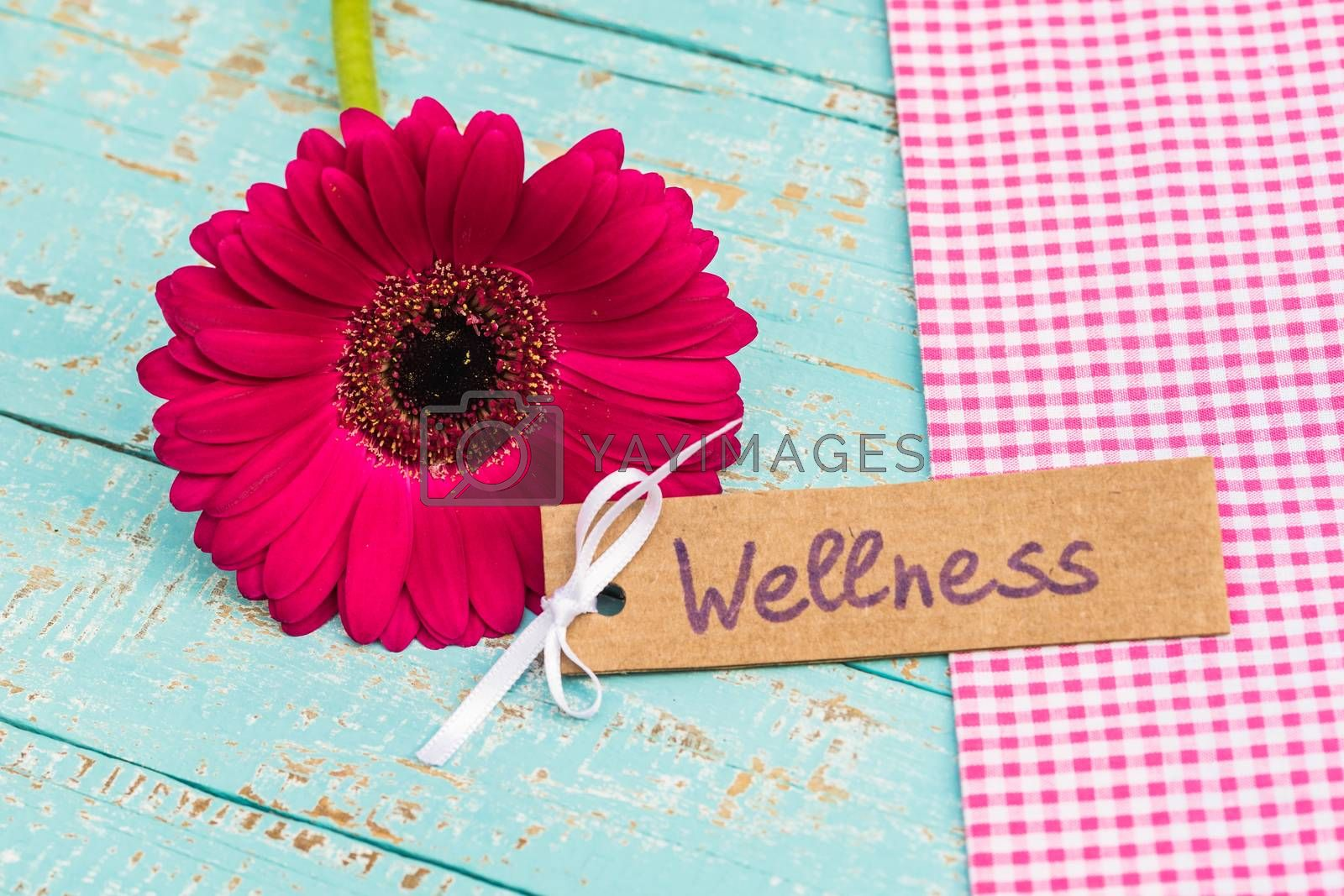 Tag with word wellness and beautiful flower as gift