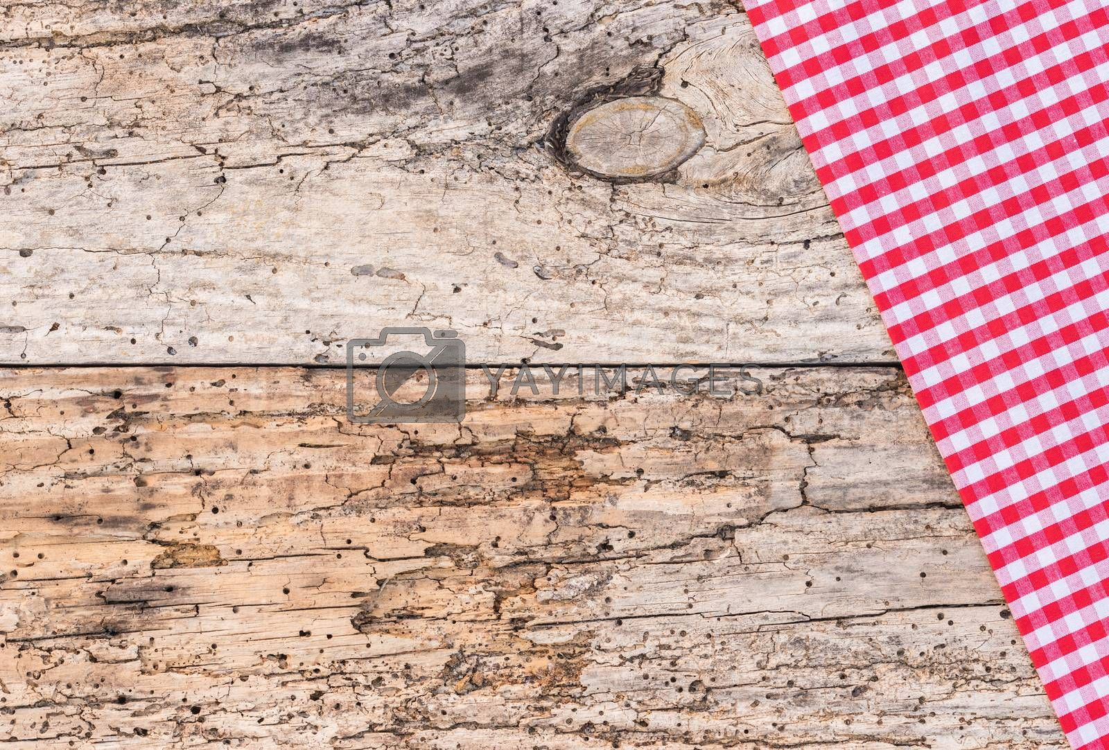 Old wooden table covered with red tablecloth, top view, copy space
