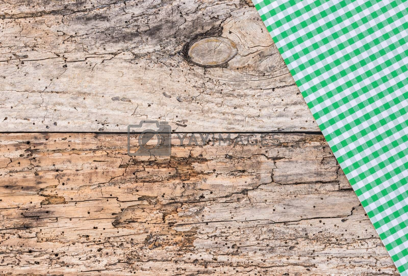Green tablecloth on rustic old wood, top view, copy space