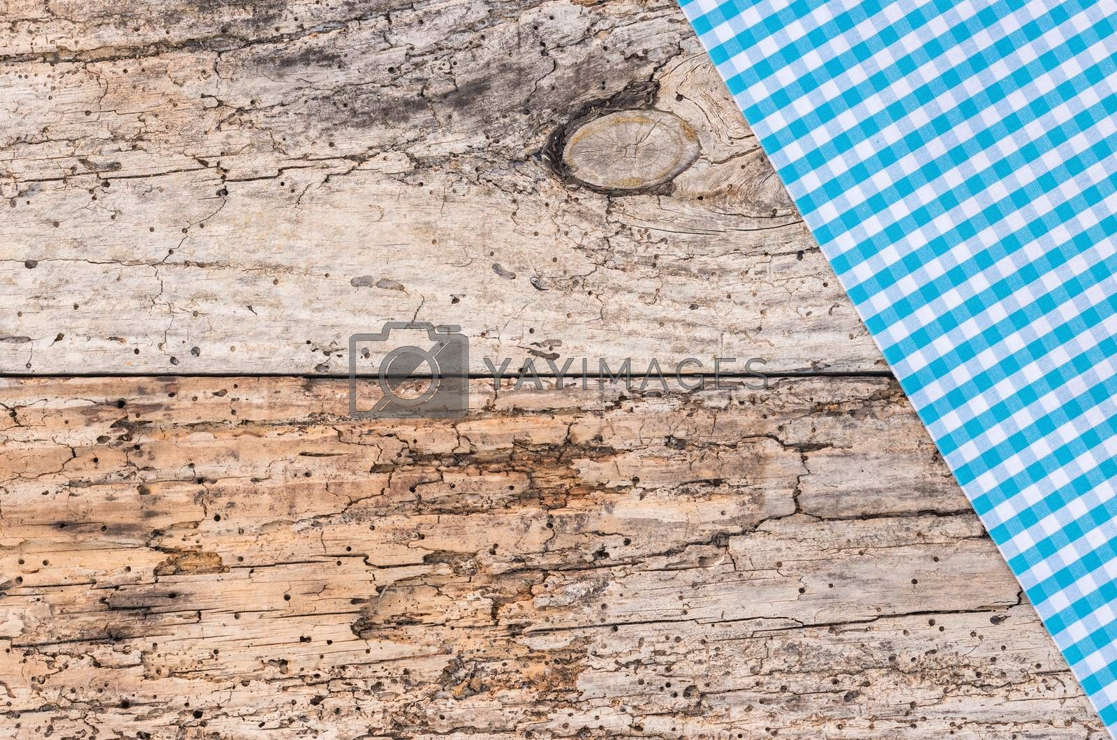 Rustic blue checked table-cloth fabric on old wooden table, top view, copy space