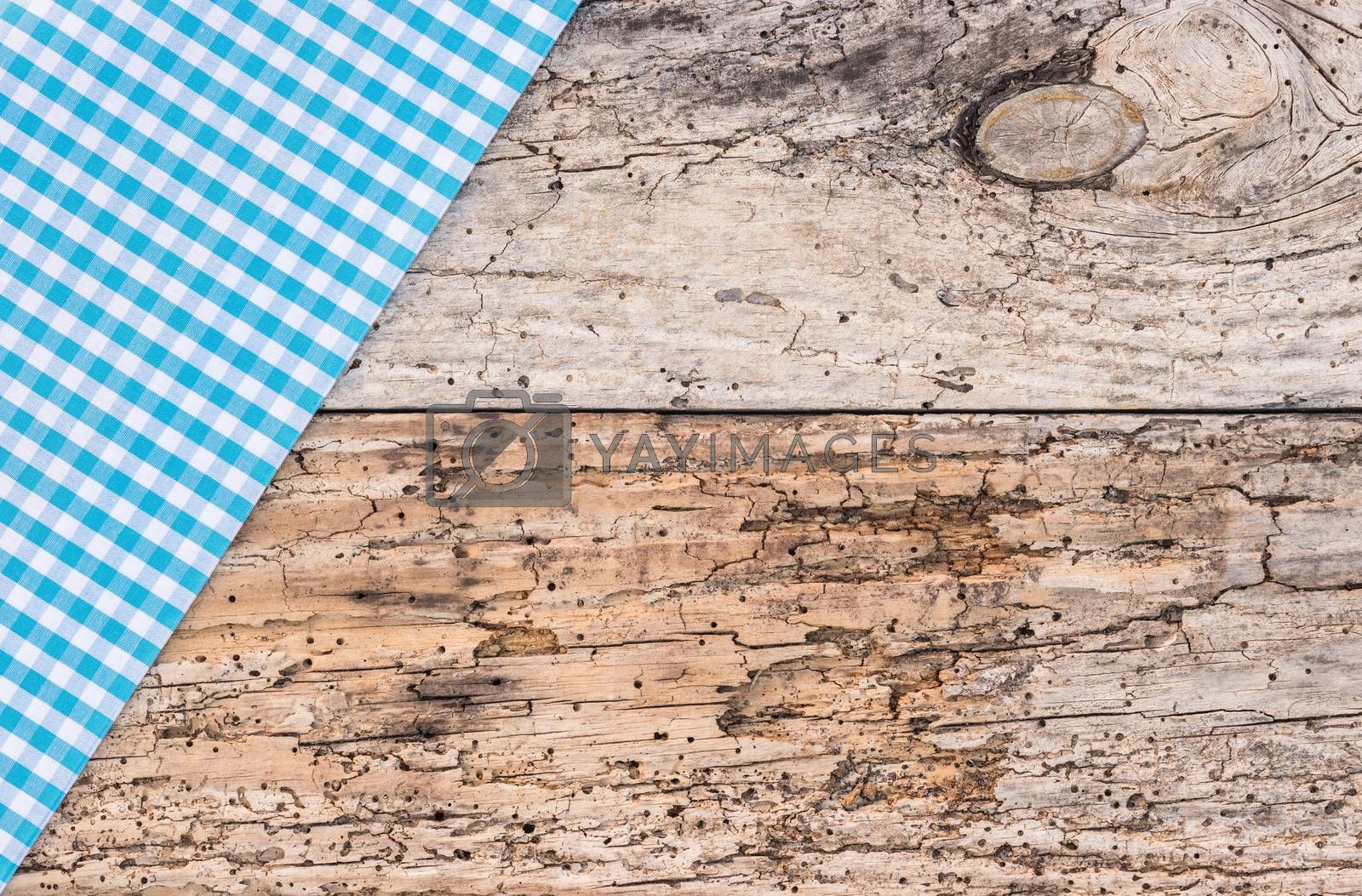 Blue tablecloth on old wooden table background, top view, copy space