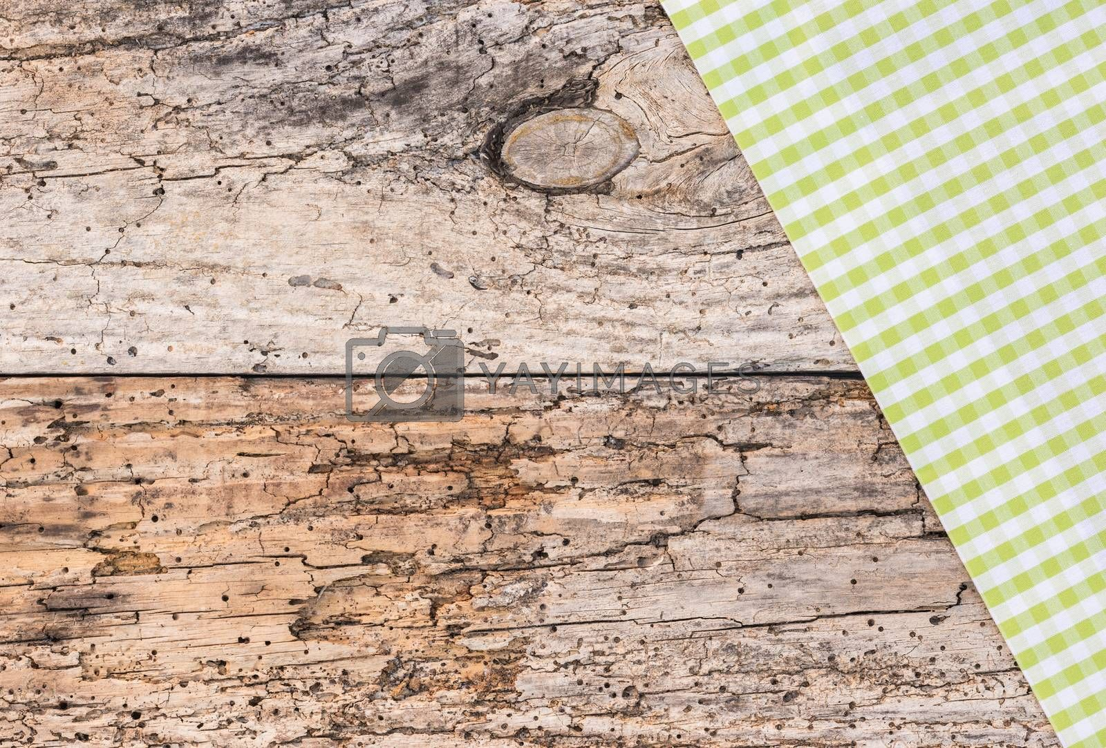 Green checked table-cloth on old rustic wood background, top view, copy space