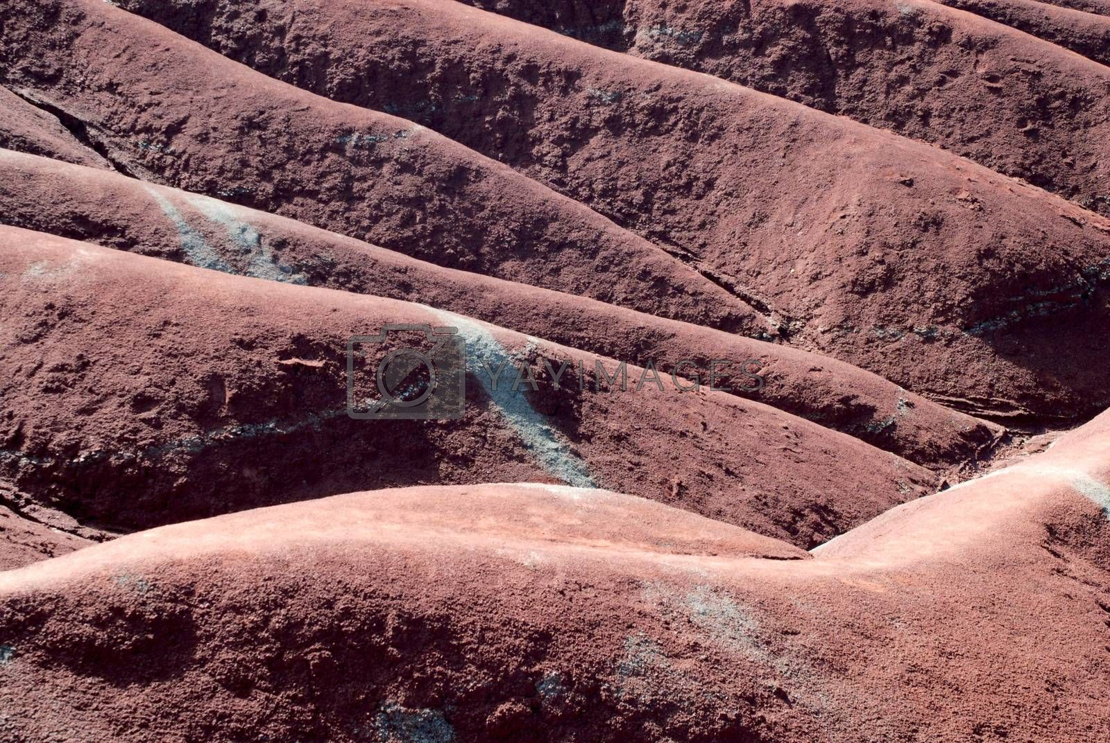 Red sedimentary clay badlands dunes background texture.