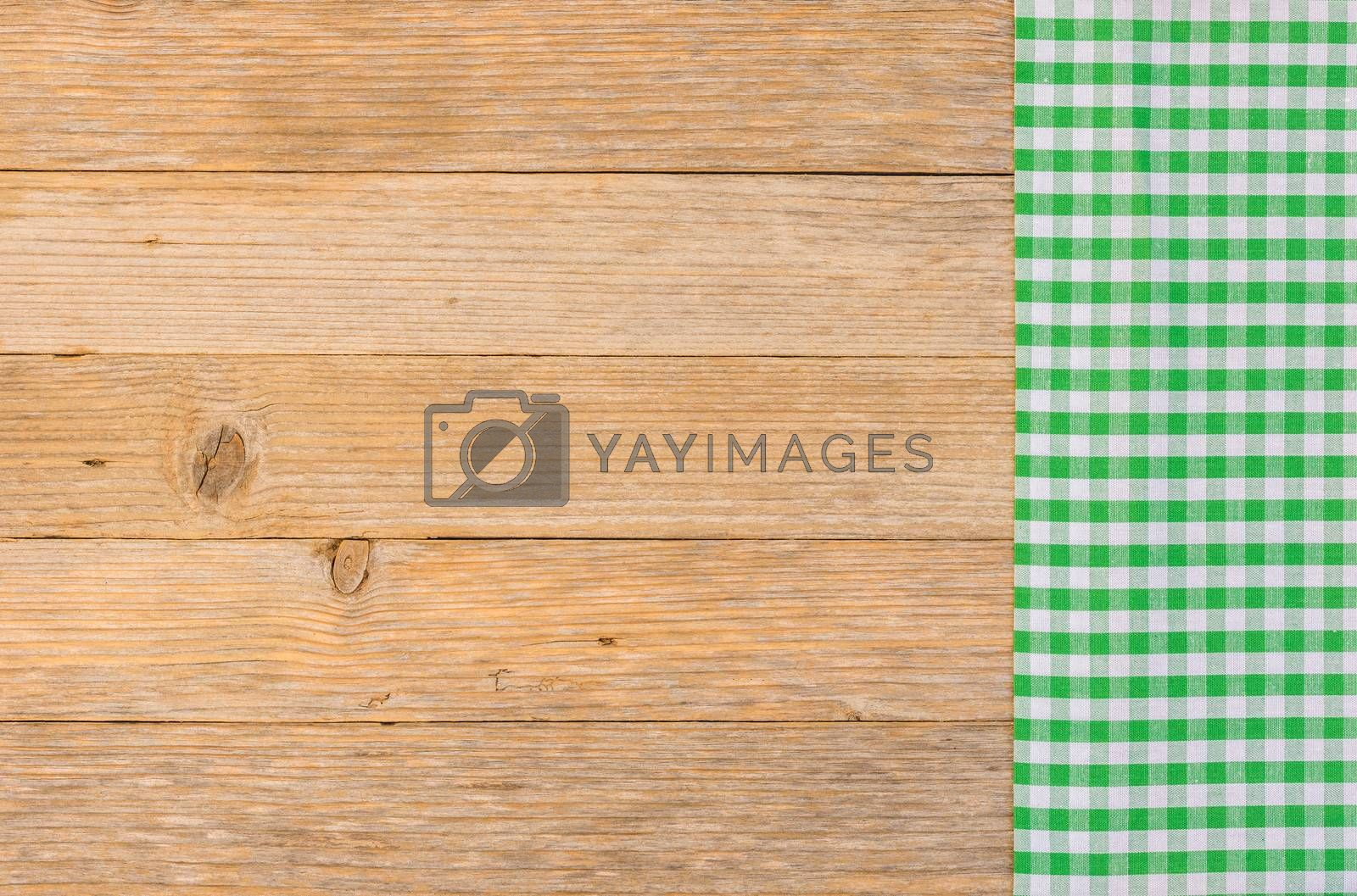 Green checked table-cloth on wooden background with copy space, top view