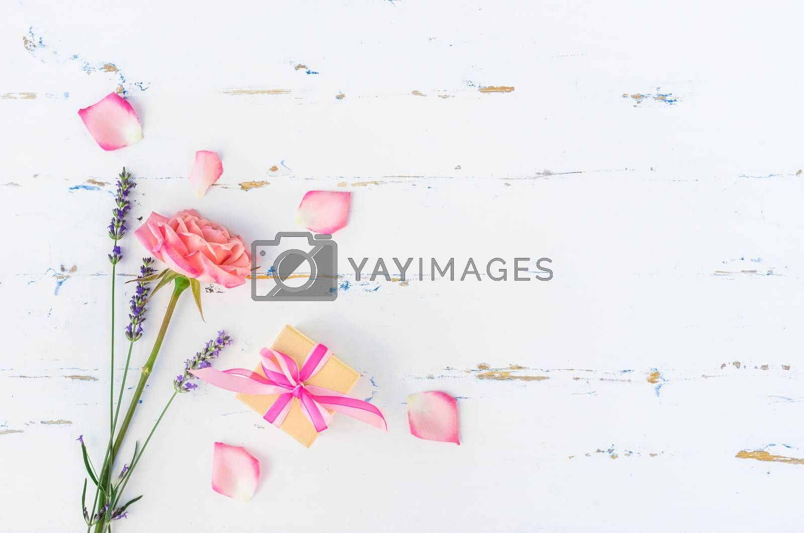 Romantic bunch of flowers with rose and lavender and small present on white wooden background with copy space