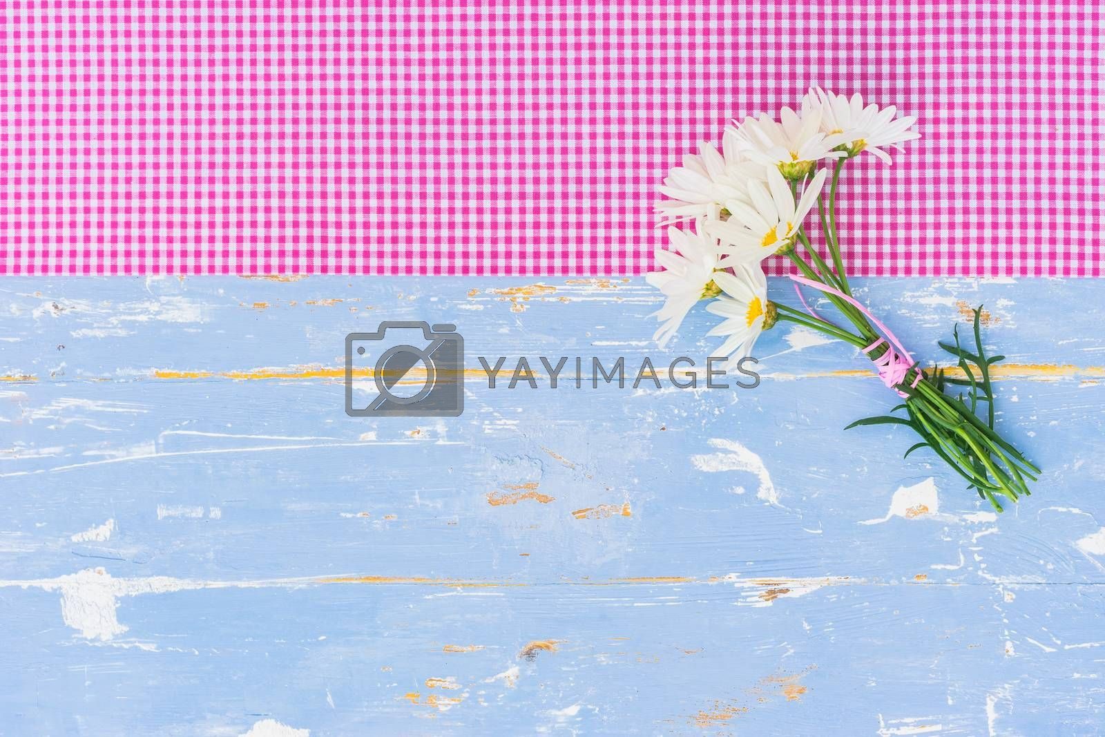 Beautiful bouquet of daisy chamomile flowers on blue wooden table background with copy space