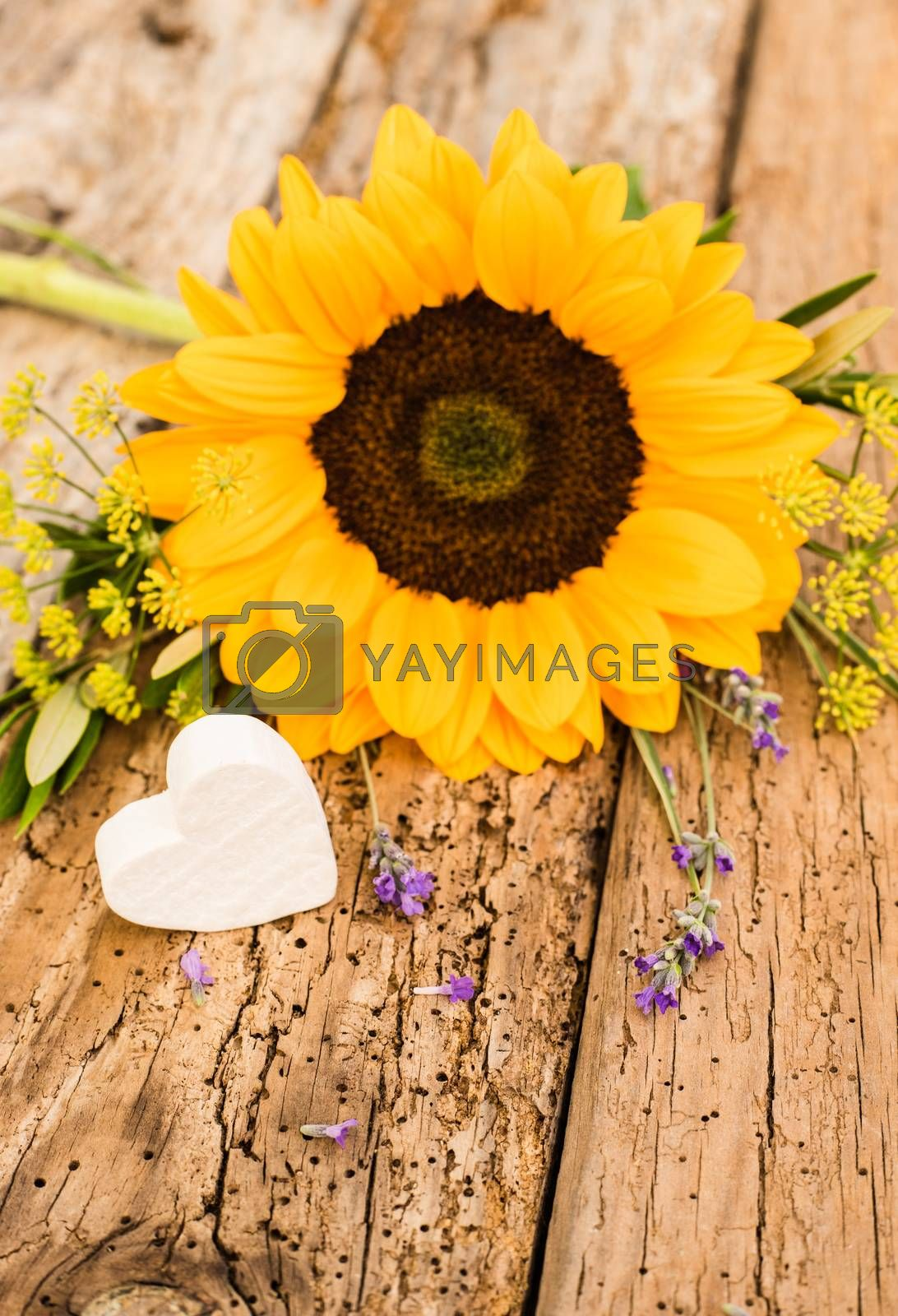 Bunch of flowers with yellow sunflower and little heart on rustic wooden background